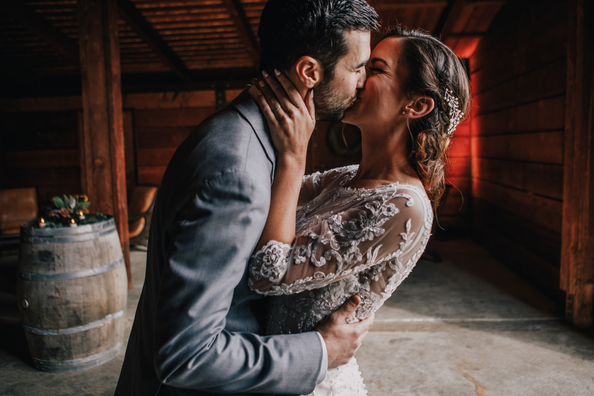 san diego wedding   photographer | groom in grey suit kissing woman in barn