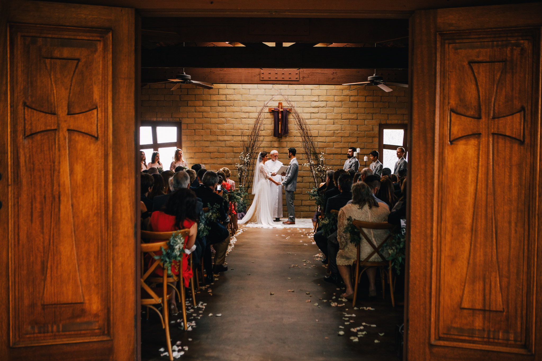 san diego wedding   photographer | bride and groom holding hands down the aisle seen through   chapel door