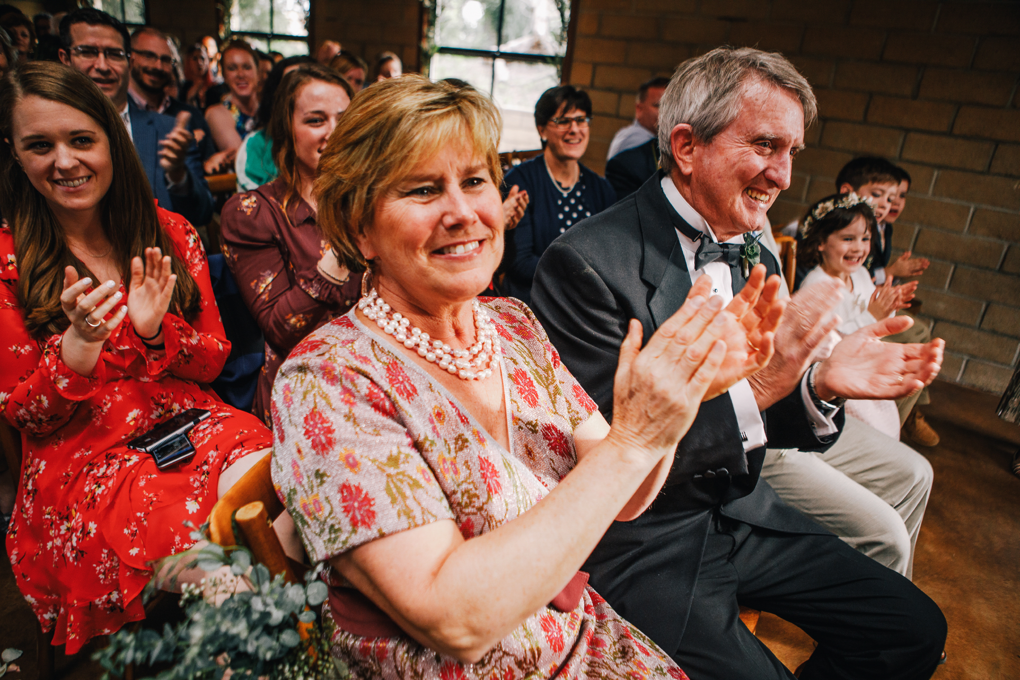 san diego wedding   photographer | middle aged woman smiling and applauding in the crowd at the   newly wed couple