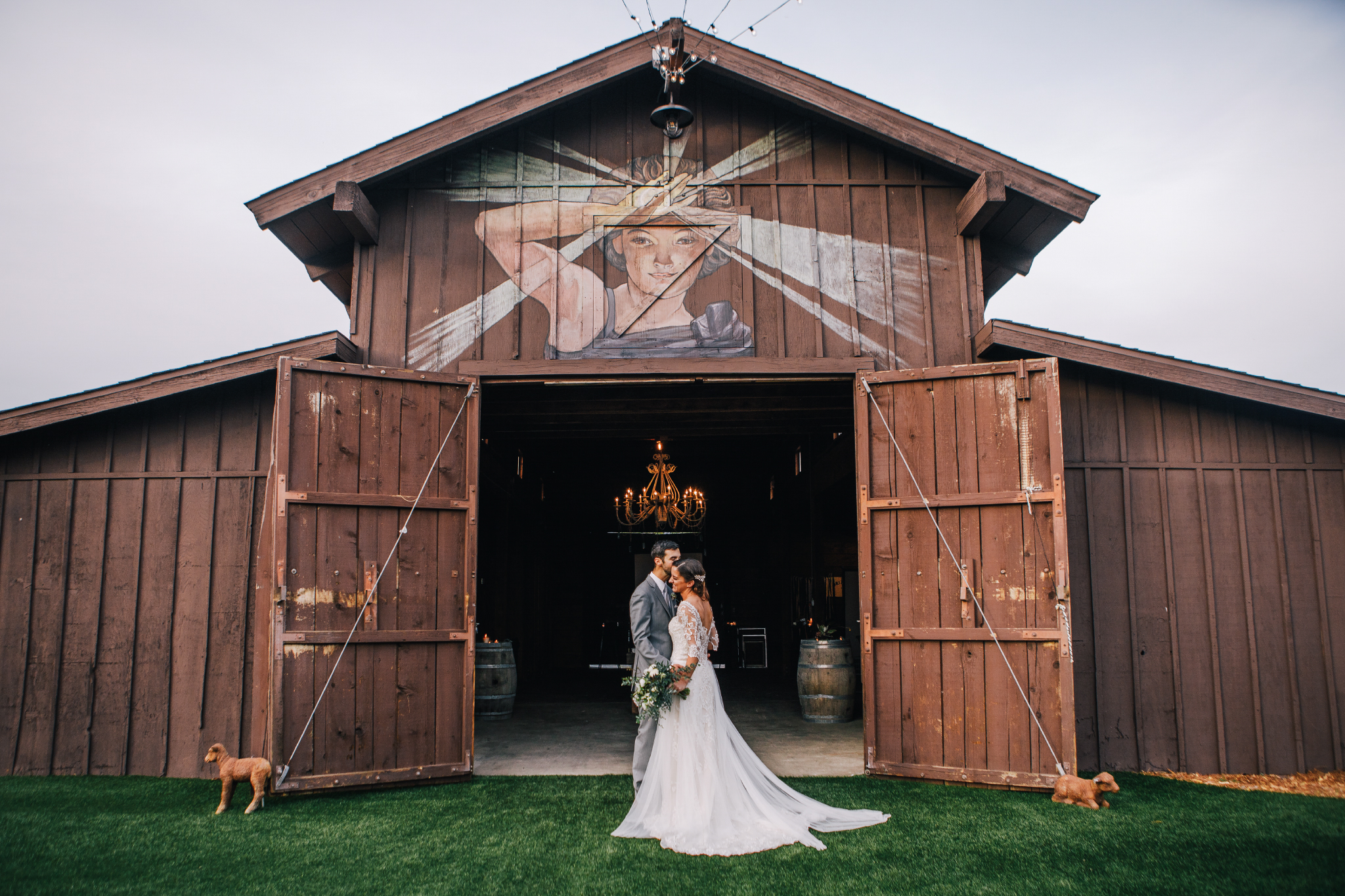 san diego wedding   photographer | bride and groom standing close to each other in front of barn   with dog on the side