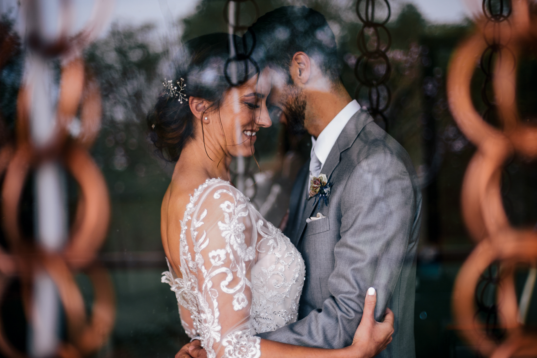 san diego wedding   photographer | married couple dancing as seen through glass window reflecting   chains hanging