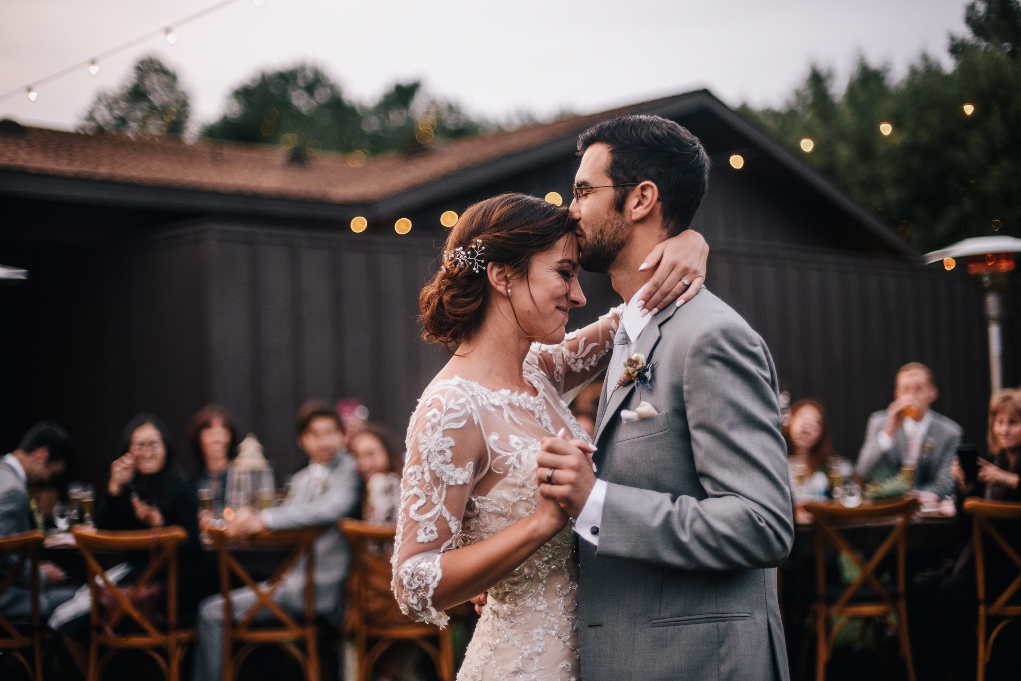 san diego wedding   photographer | bride and groom with groom kissing bride's forehead with   blurred crowd in background