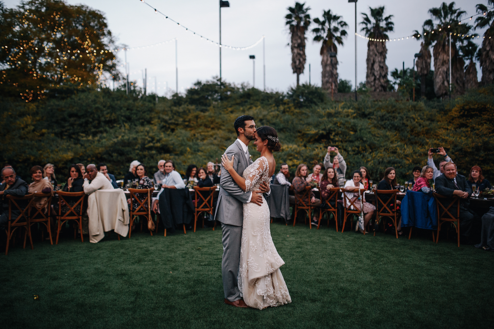 san diego wedding   photographer | bride and groom with groom kissing bride's forehead with trees   in background
