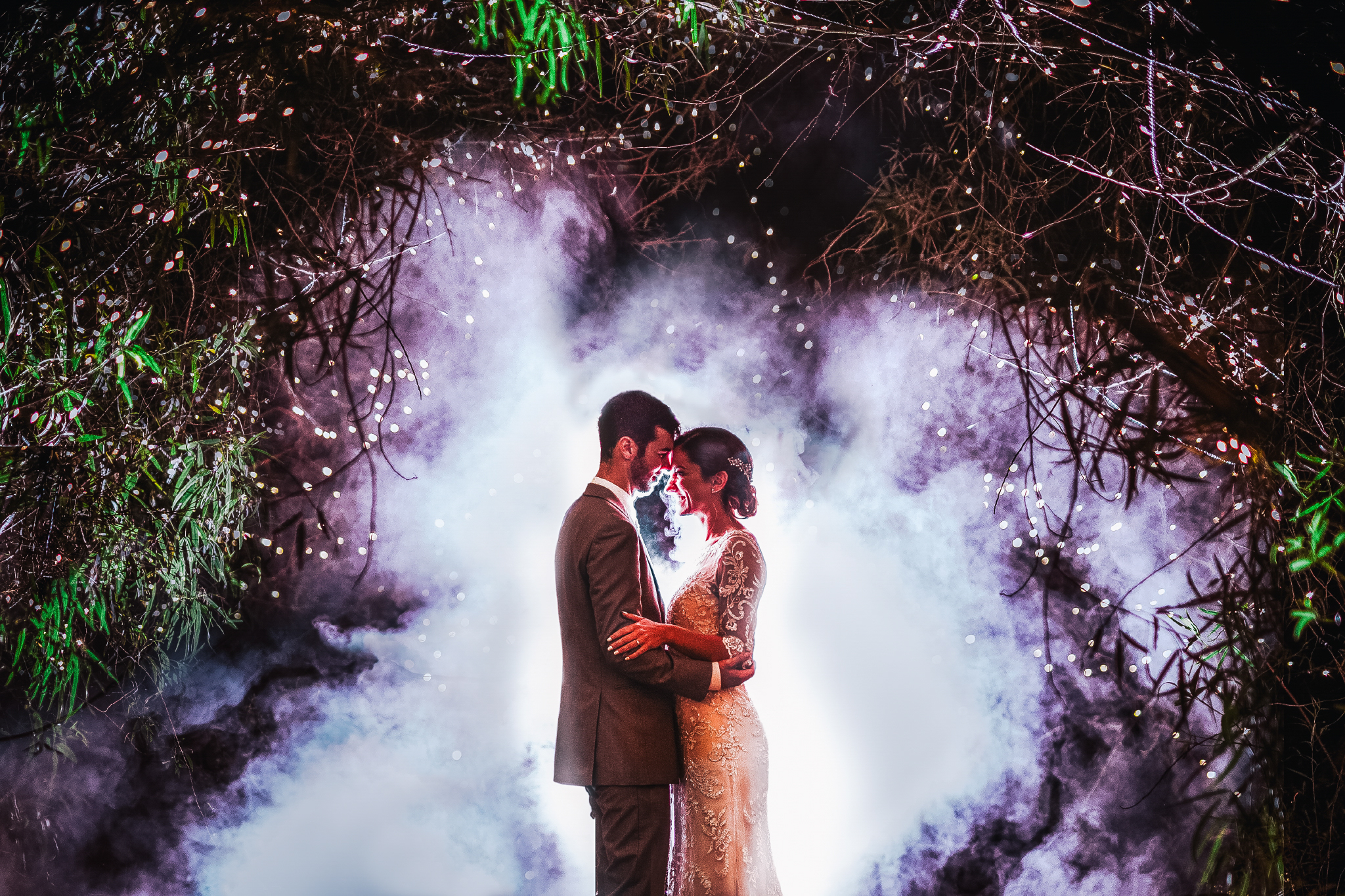 san diego wedding   photographer | bride and groom standing in front of each other with smoke   behind them under branches and lights