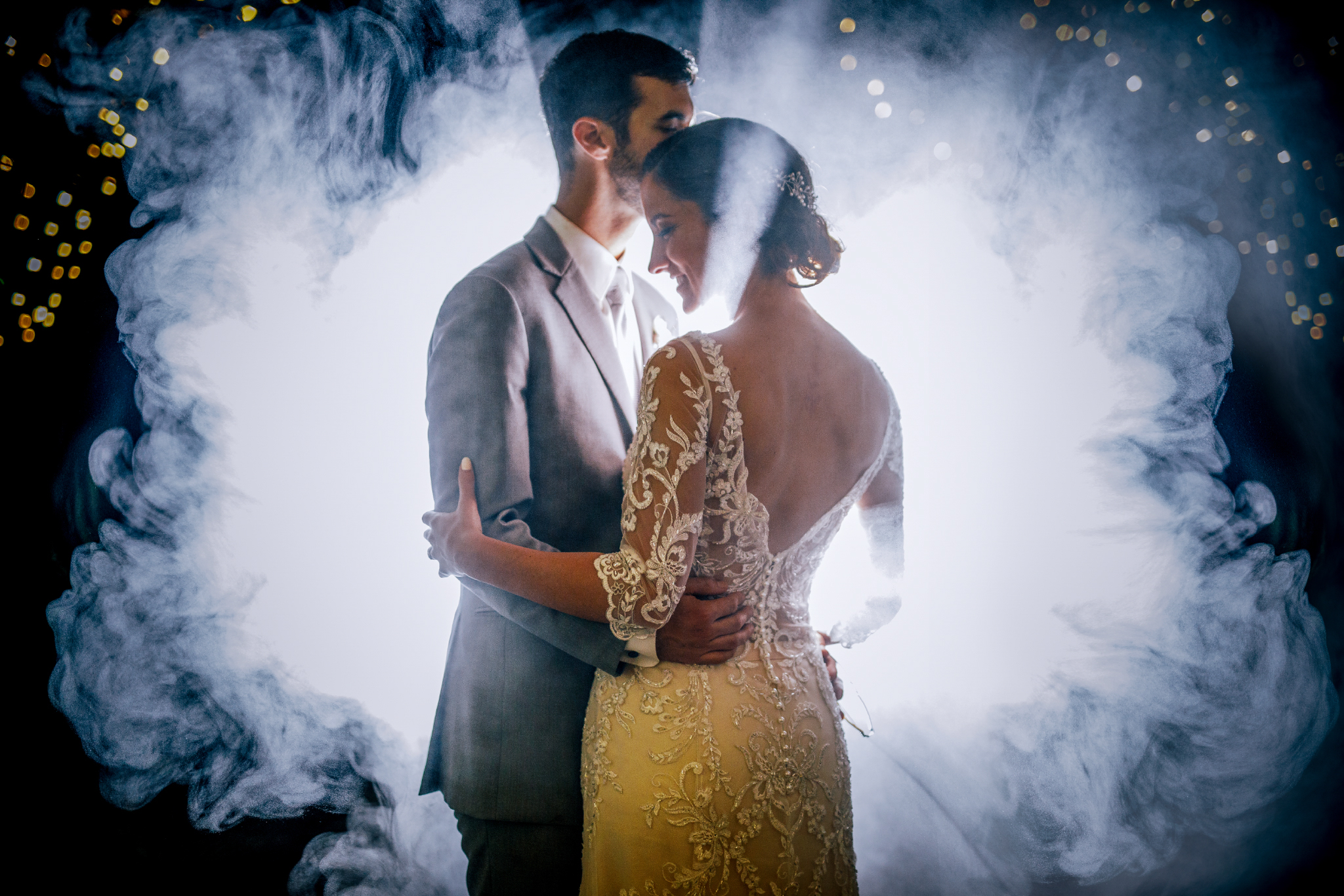 san diego wedding   photographer | groom kissing bride's forehead while holding her waist with   smoke behind them
