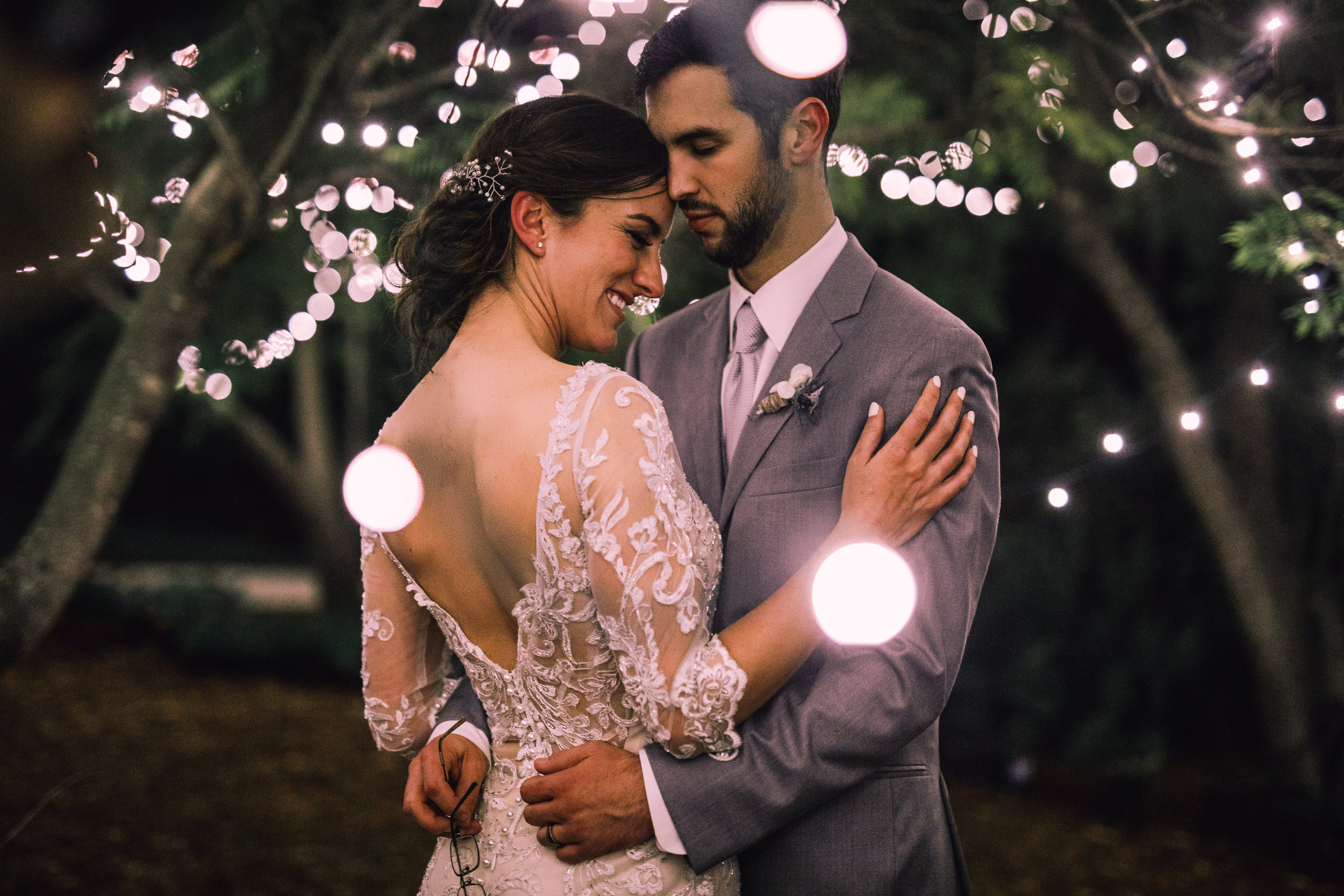 san diego wedding   photographer | groom dancing with bride with bride's arm on groom's arm under   lights and branches
