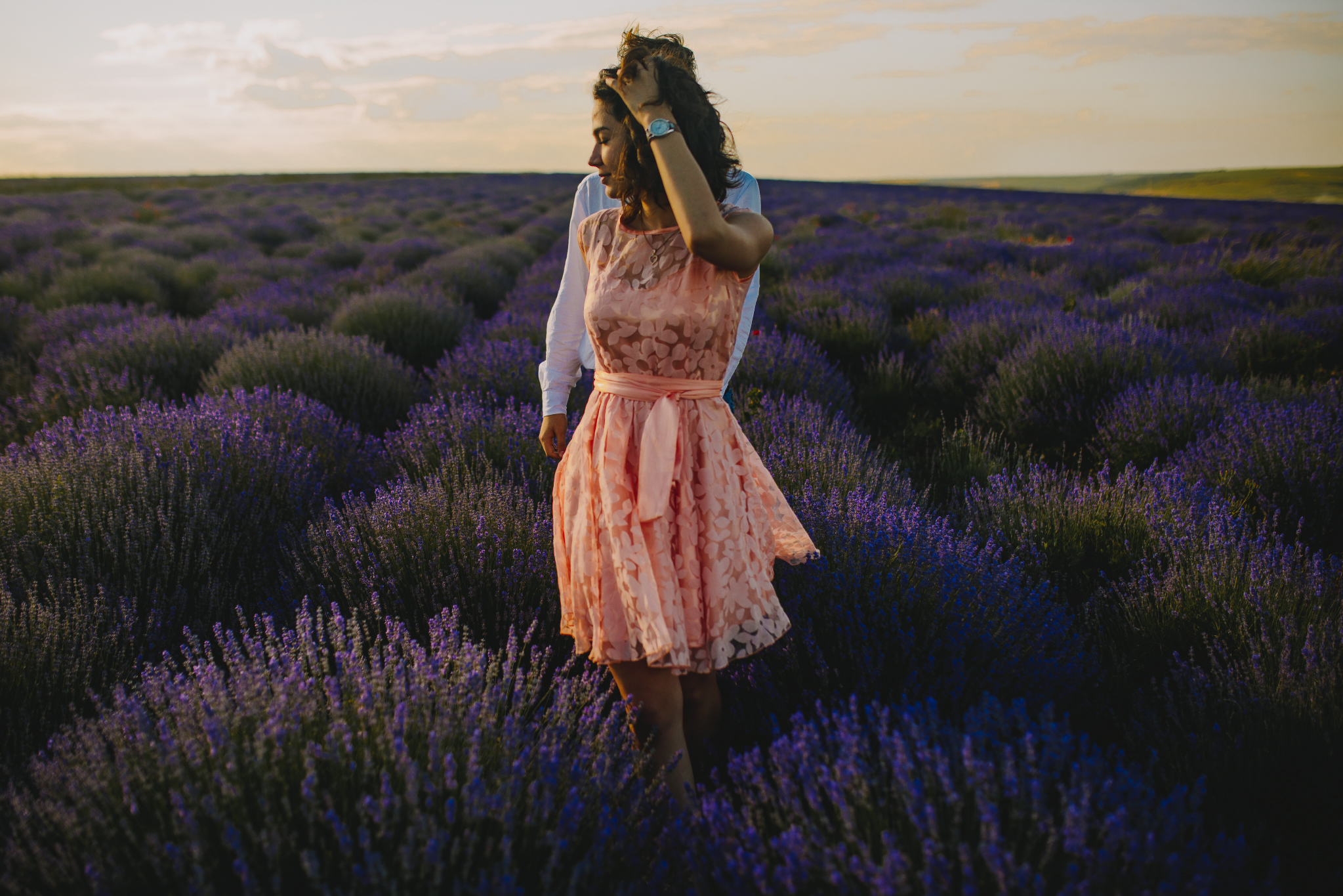 san diego wedding   photographer | woman in pink floral dress playing with hair and pulling hand   of man in white polo in lavender   fields