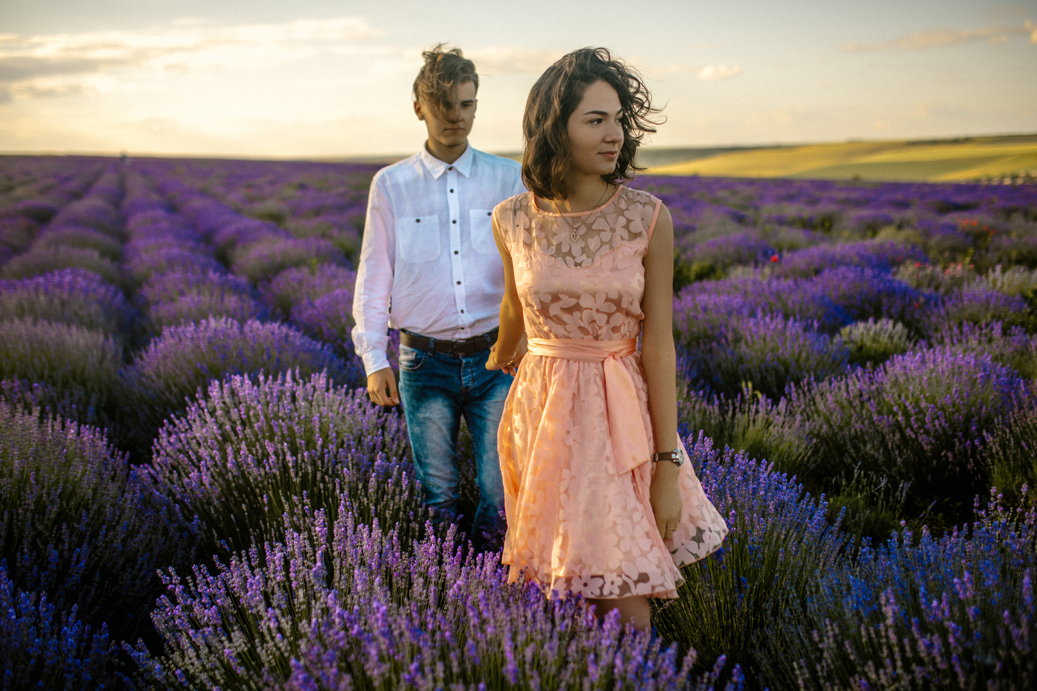 san diego wedding   photographer | woman in pink floral dress looking to her left and pulling   hand of blonde man in lavender fields