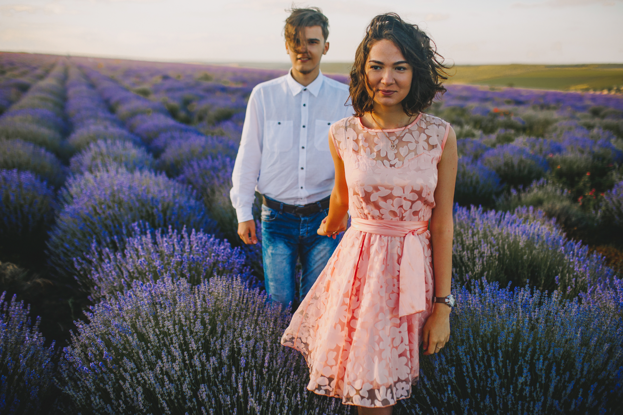 san diego wedding   photographer | woman in pink floral dress looking to her right and pulling   hand of blonde man in lavender fields