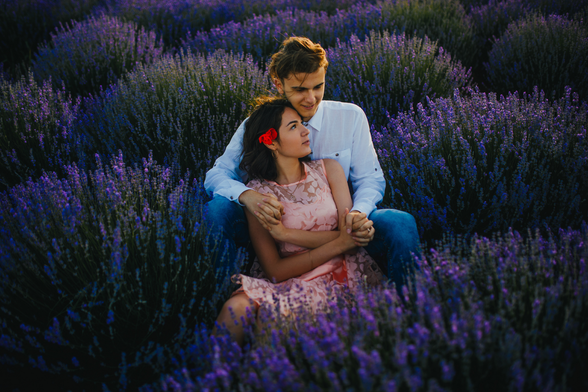 san diego wedding   photographer | woman in pink floral dress leaning on blonde man's lap and   holding his hands in lavender fields