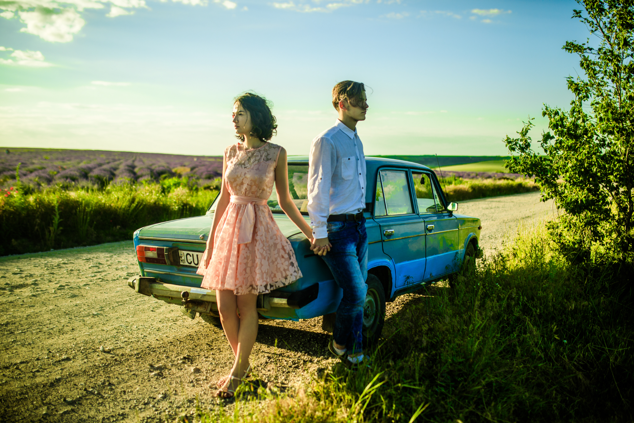 san diego wedding   photographer | woman in pink floral dress and blonde man holding hands and   leaning on blue car