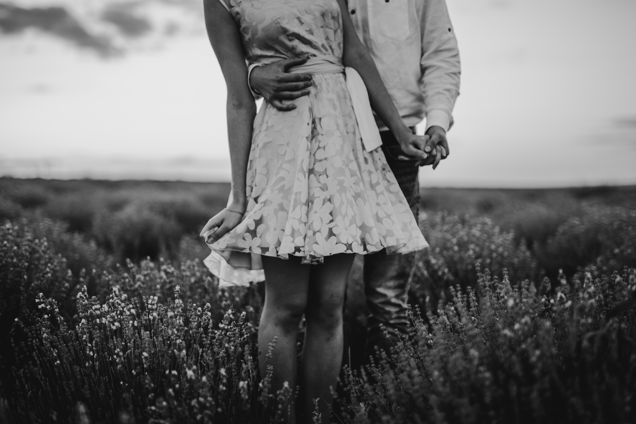 san diego wedding   photographer | monotone below-neck shot of man hugging woman in pink floral   dress's waist and holding her hand
