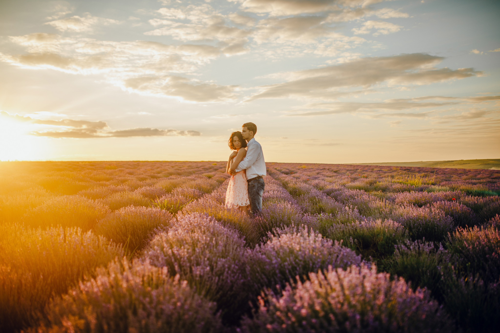 san diego wedding   photographer | side view shot of blonde man hugging woman in pink floral   dress from behind in lavender fields