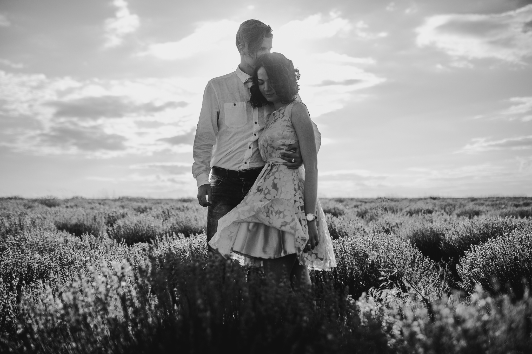 san diego wedding   photographer | monotone shot of blonde man hugging woman in pink floral   dress's waist and kissing her head