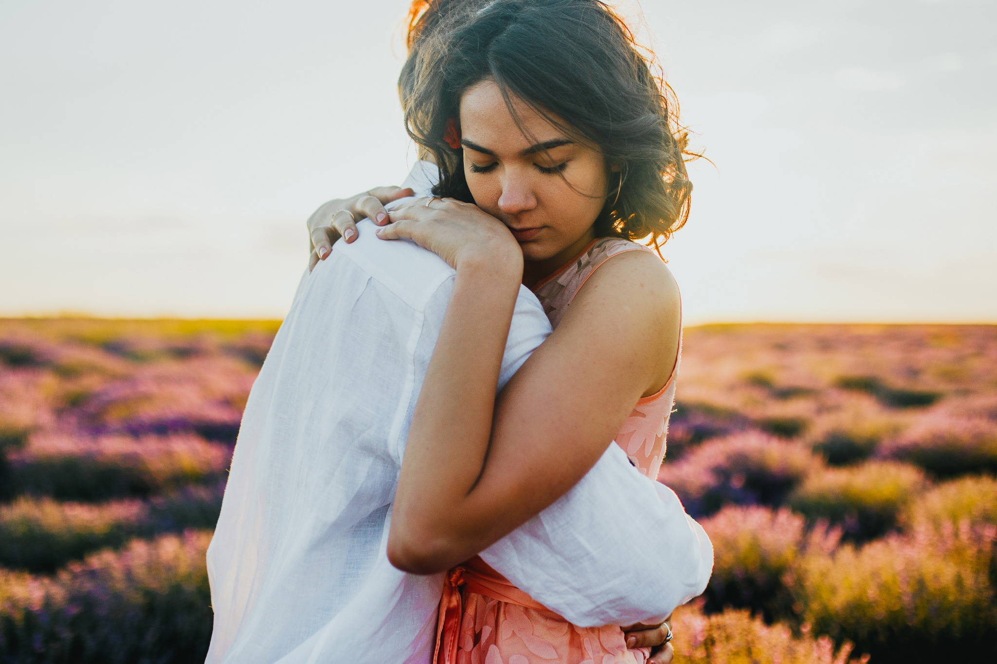san diego wedding   photographer | woman in pink floral dress tightly hugging blonde man in   lavender fields