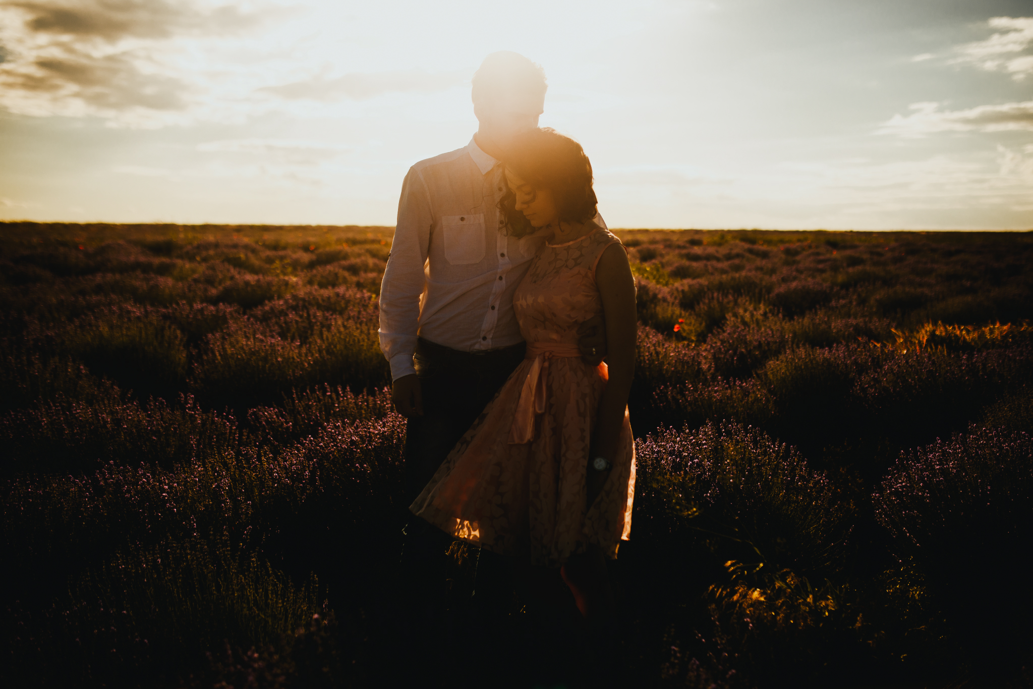 san diego wedding   photographer | whole body shot of man in white polo holding waist of woman in   pink floral dress against sunlight in lavender fields