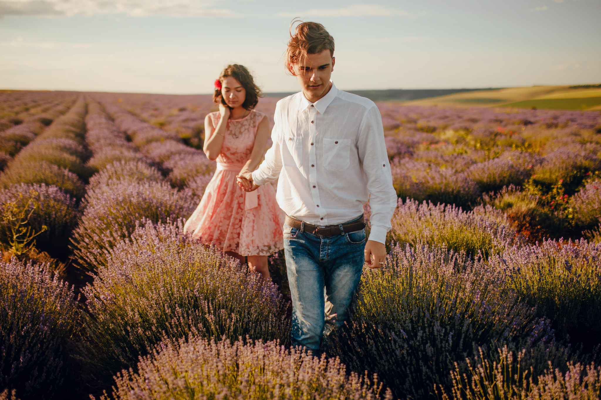 san diego wedding   photographer | blonde man in white polo holding hand of woman in pink floral   dress facing camera in lavender fields