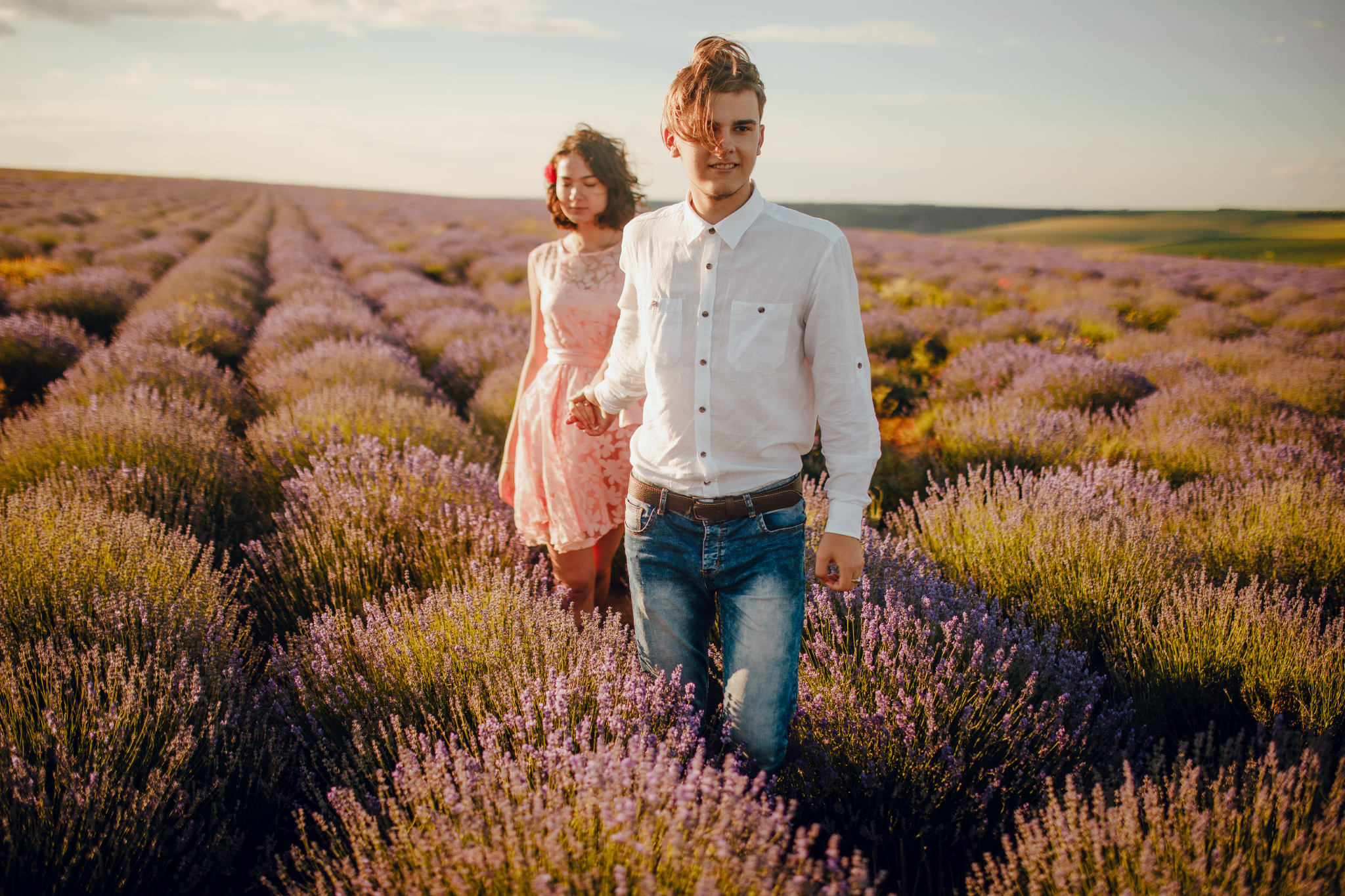 san diego wedding   photographer | blonde man in white polo holding hand of woman in pink floral   dress facing camera and smiling in lavender fields