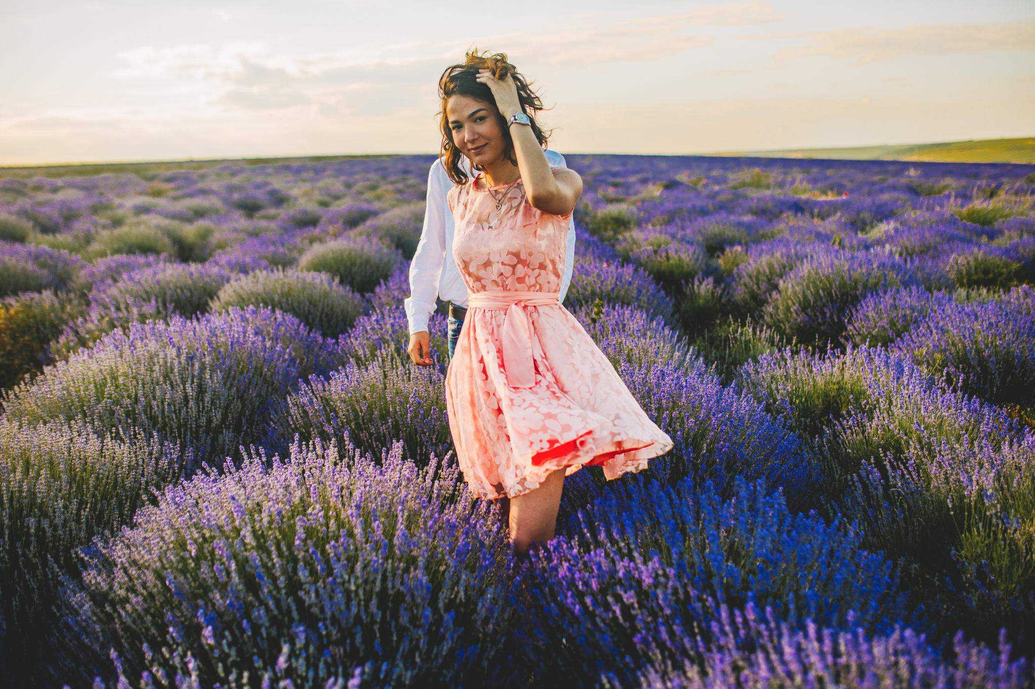san diego wedding   photographer | woman in pink floral dress smiling at camera and touching hair   with man in polo behind her in lavender fields