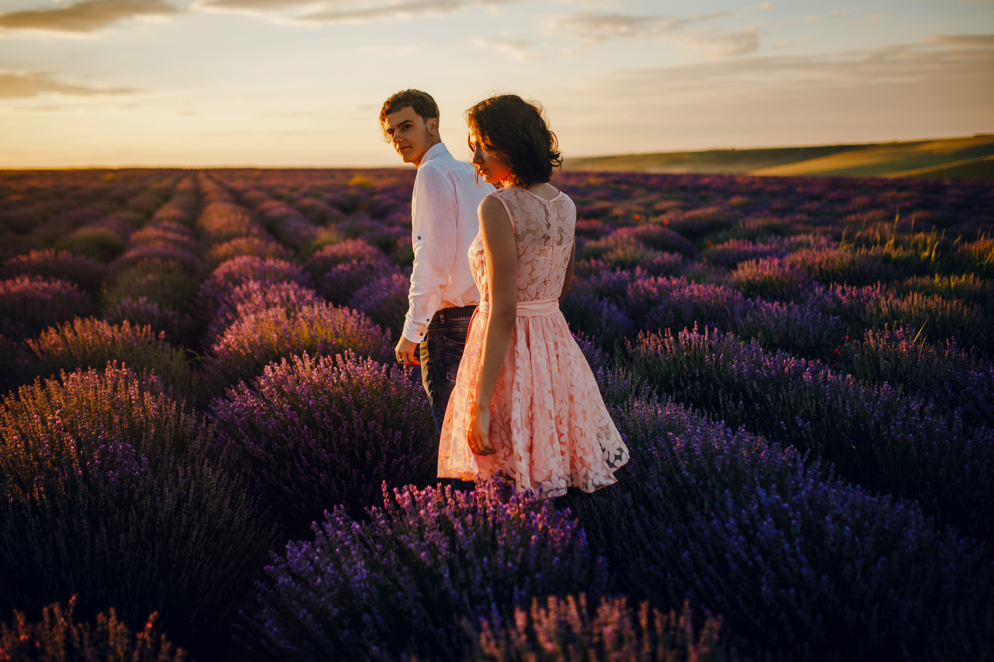 san diego wedding   photographer | woman in pink floral dress looking back while holding hand of   blonde man in lavender fields during sunset