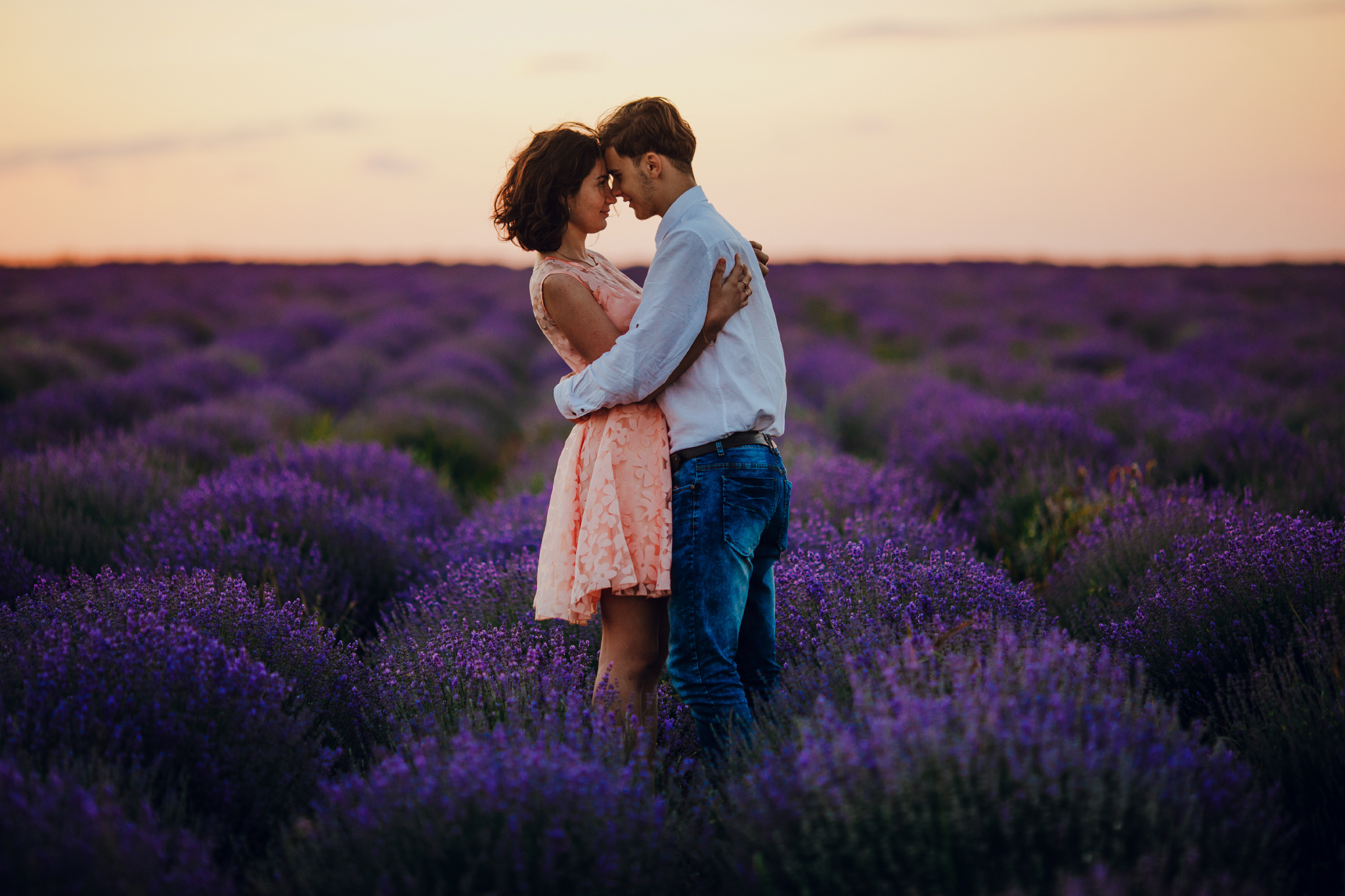 san diego wedding   photographer | woman in pink floral dress and blonde man hugging in lavender   fields against pink sky
