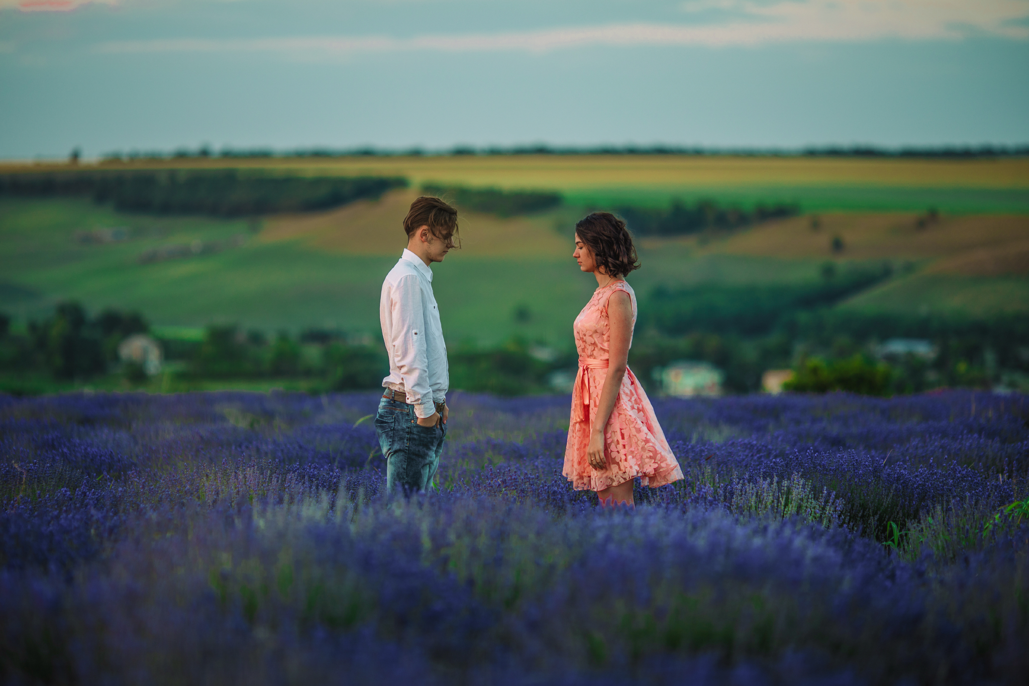 san diego wedding   photographer | woman in pink floral dress and blonde man a few feet apart and   looking down at lavender fields with blue-green filter
