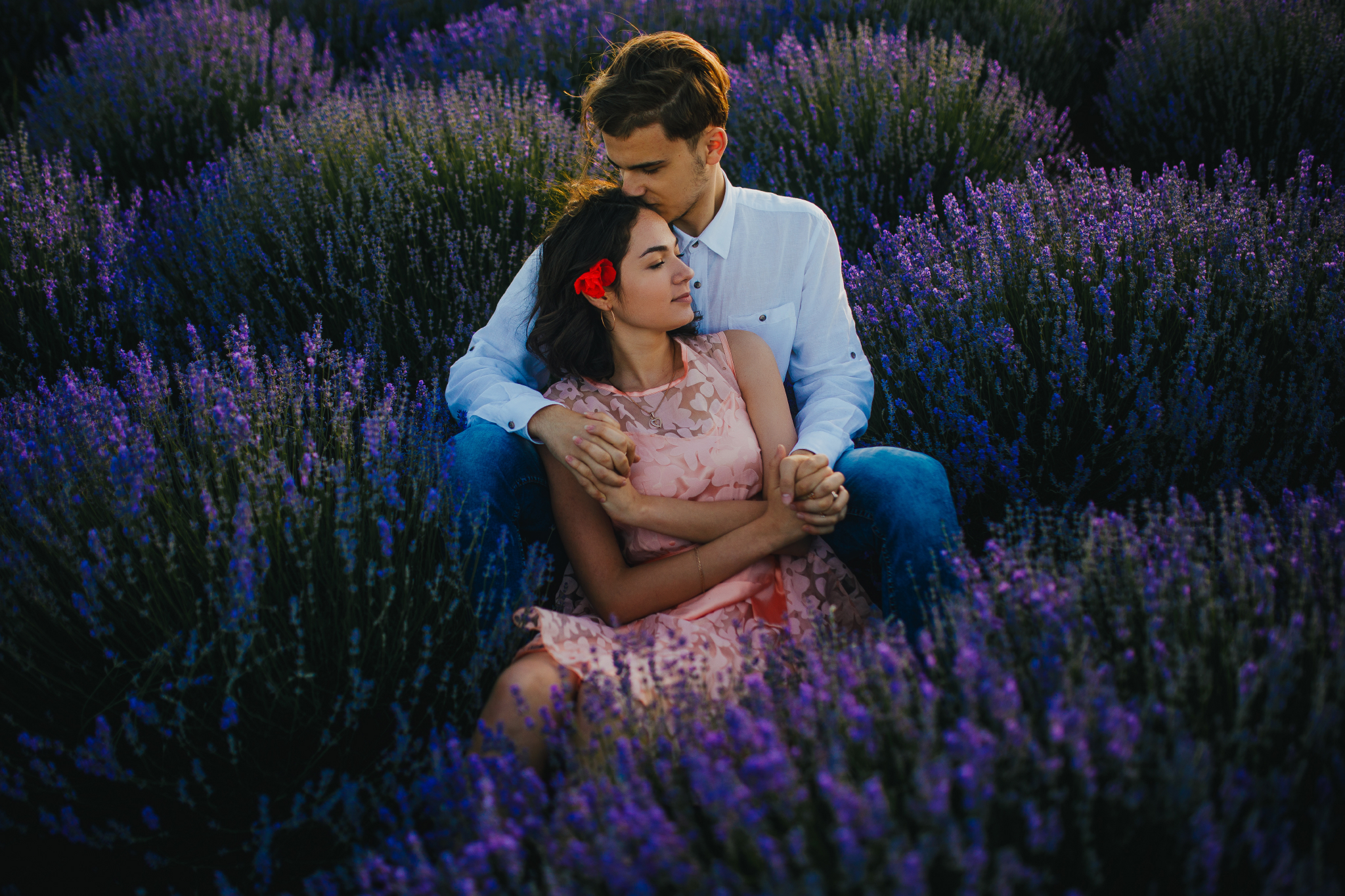 san diego wedding   photographer | slightly smiling woman in pink floral dress leaning on blonde   man's lap kissing her forehead in lavender fields