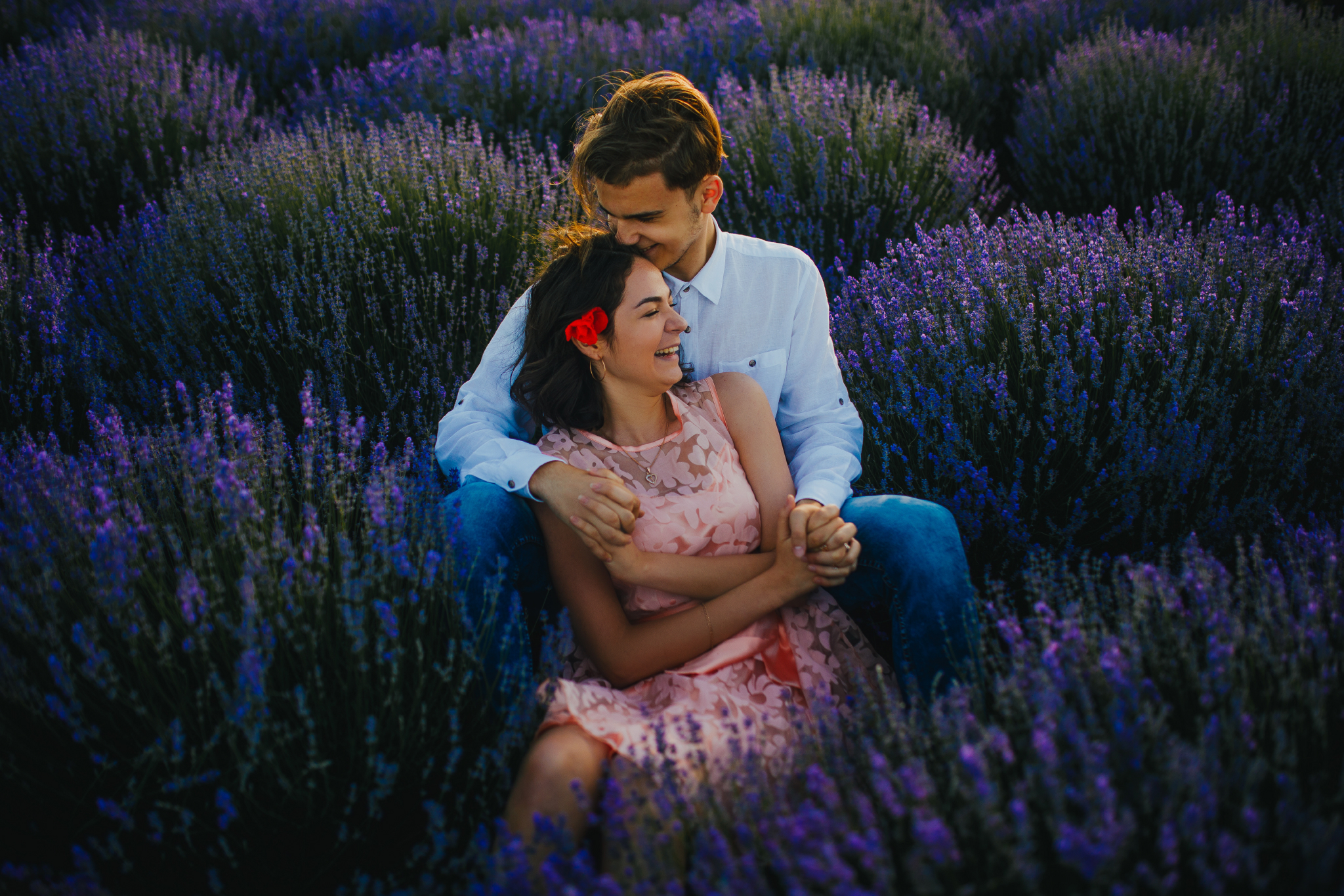 san diego wedding   photographer | laughing woman in pink floral dress leaning on blonde man's   lap kissing her forehead in lavender fields