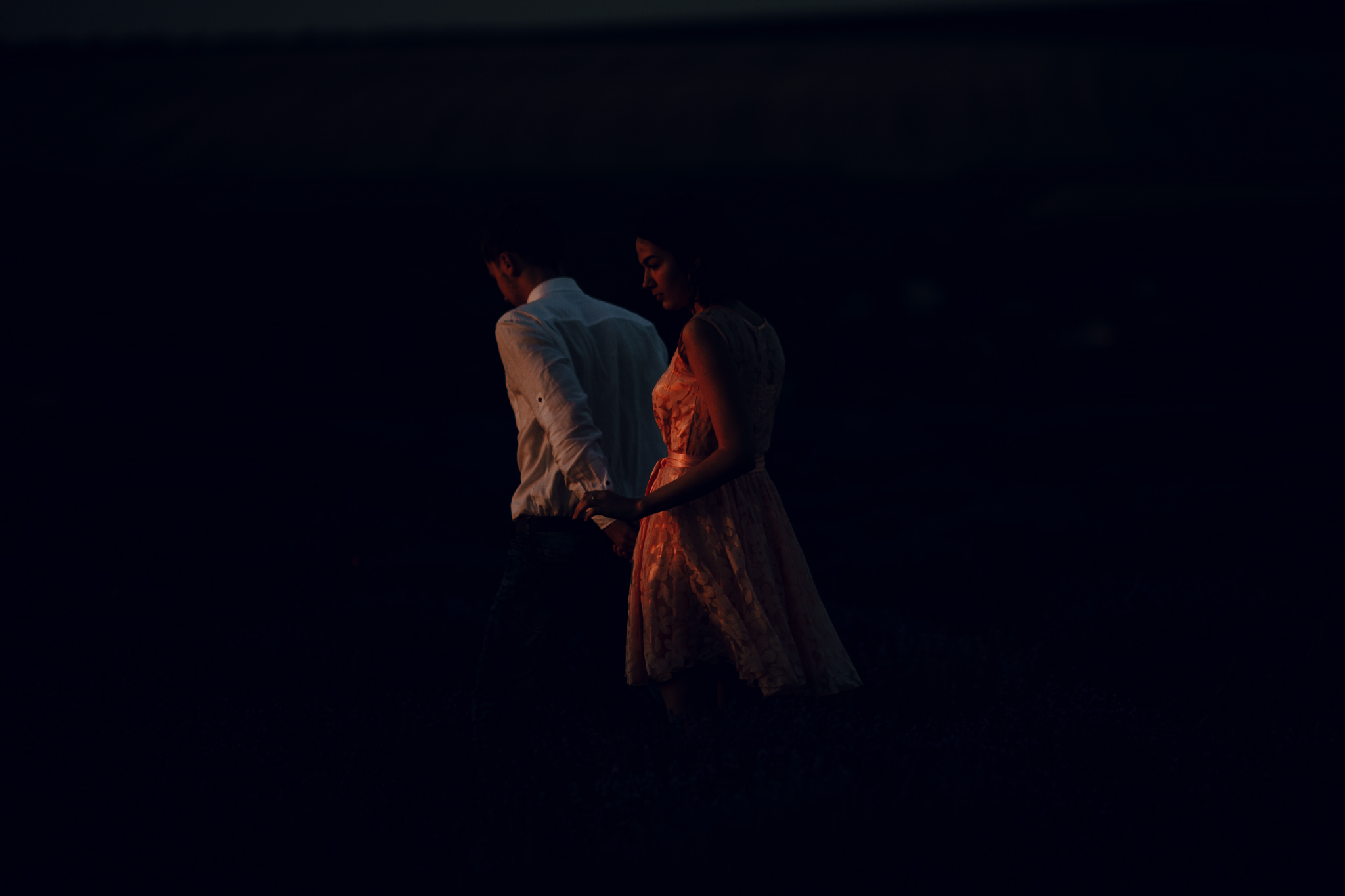 san diego wedding   photographer | woman in pink floral dress and blonde man holding hands   against dark sky