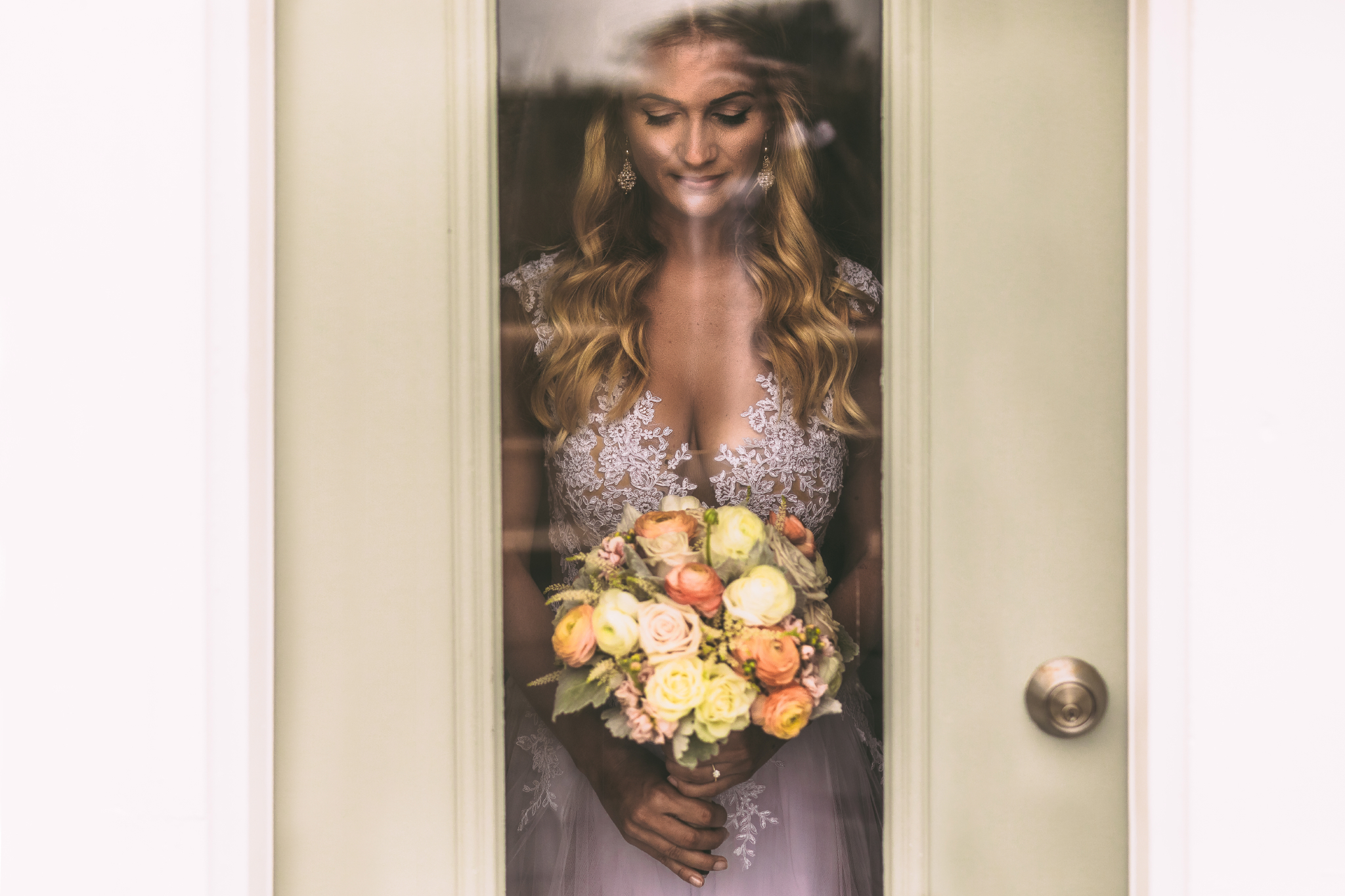 san diego wedding   photographer | woman in white dress holding bouquet of flowers looking   through glass window of door
