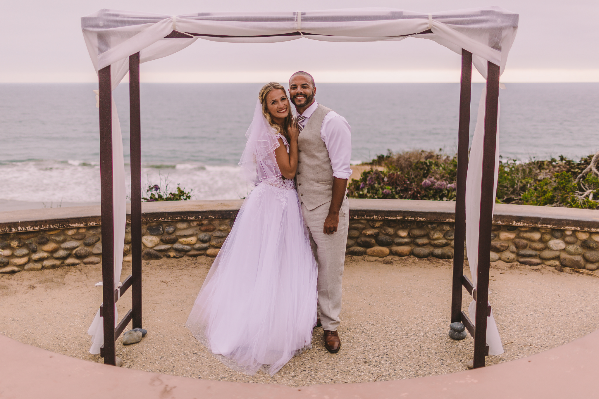 san diego wedding   photographer | married couple smiling with bride leaning against groom's   chest with the ocean in the background