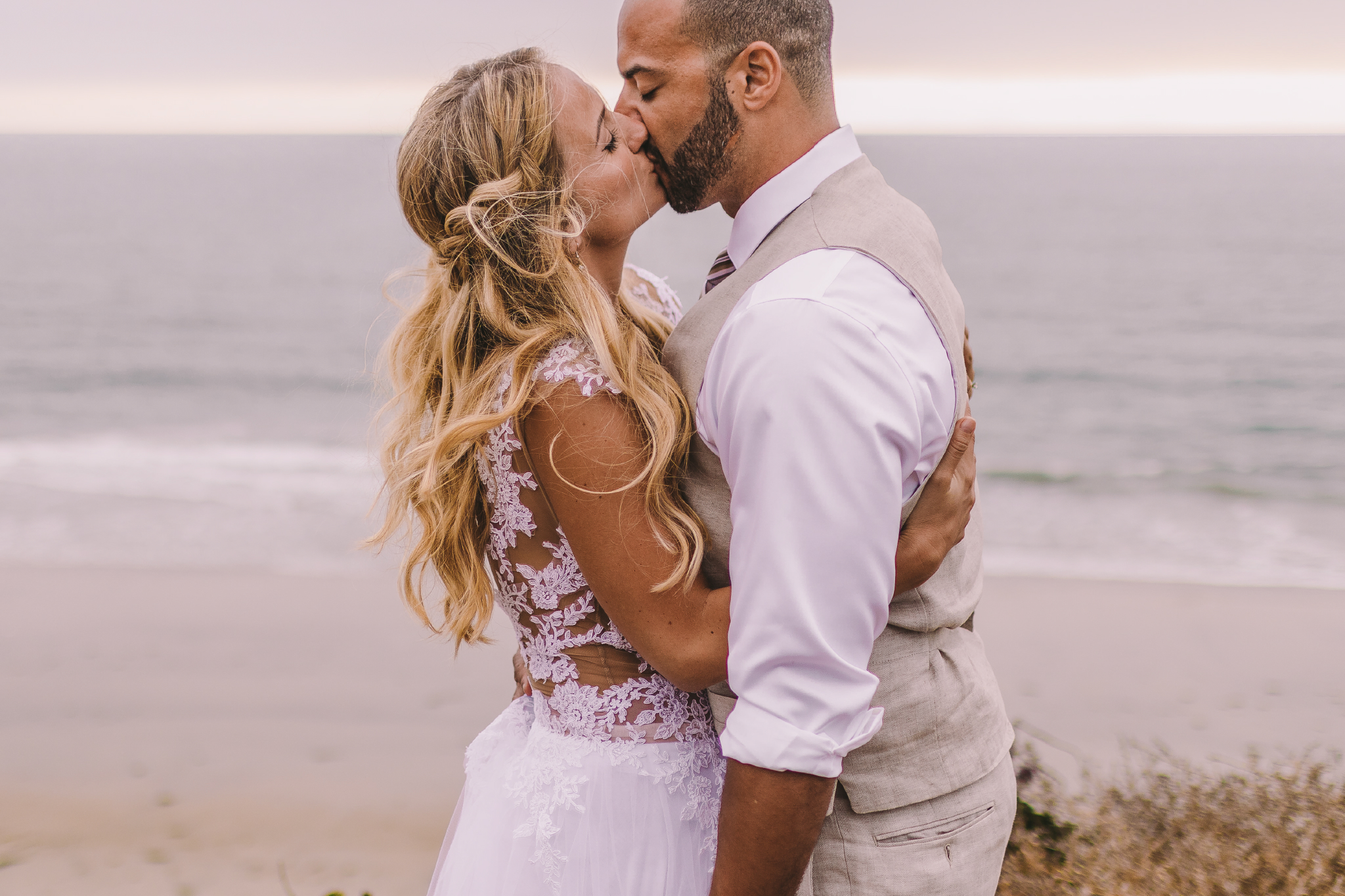 san diego wedding   photographer | married couple kissing each other with woman's arms around   man's back on sea