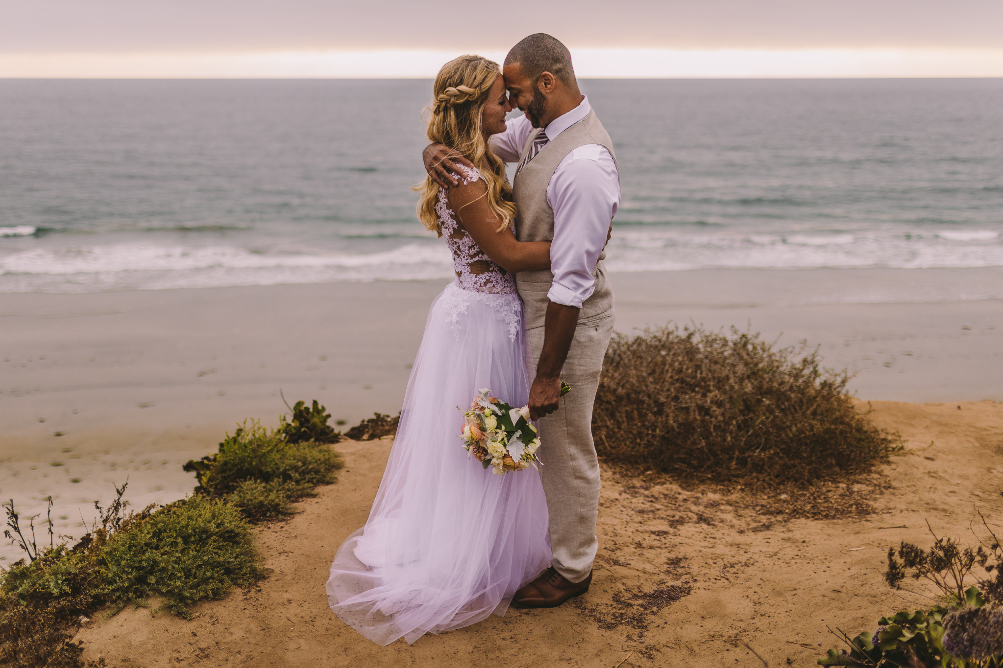 san diego wedding   photographer | couple holding each other with man holding bouquet of flowers   on sea cliff