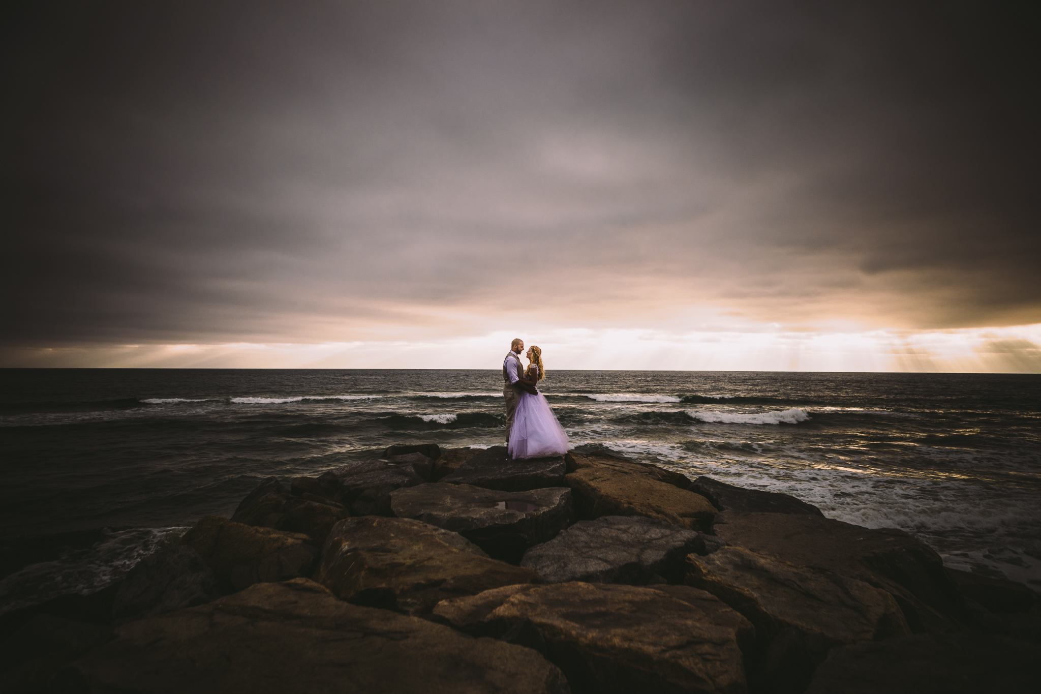 san diego wedding   photographer | married couple looking at each other while holding each other   on rocky shore with sunrays seen from afar