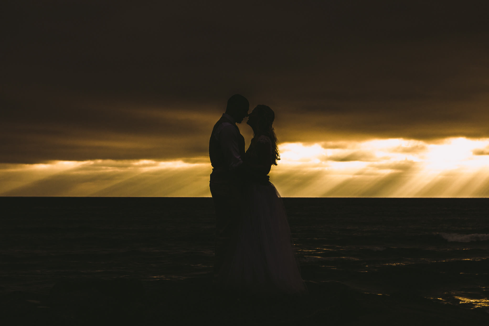 san diego wedding   photographer | silhouette of married couple looking at each other with   sunrays in the background seen from afar
