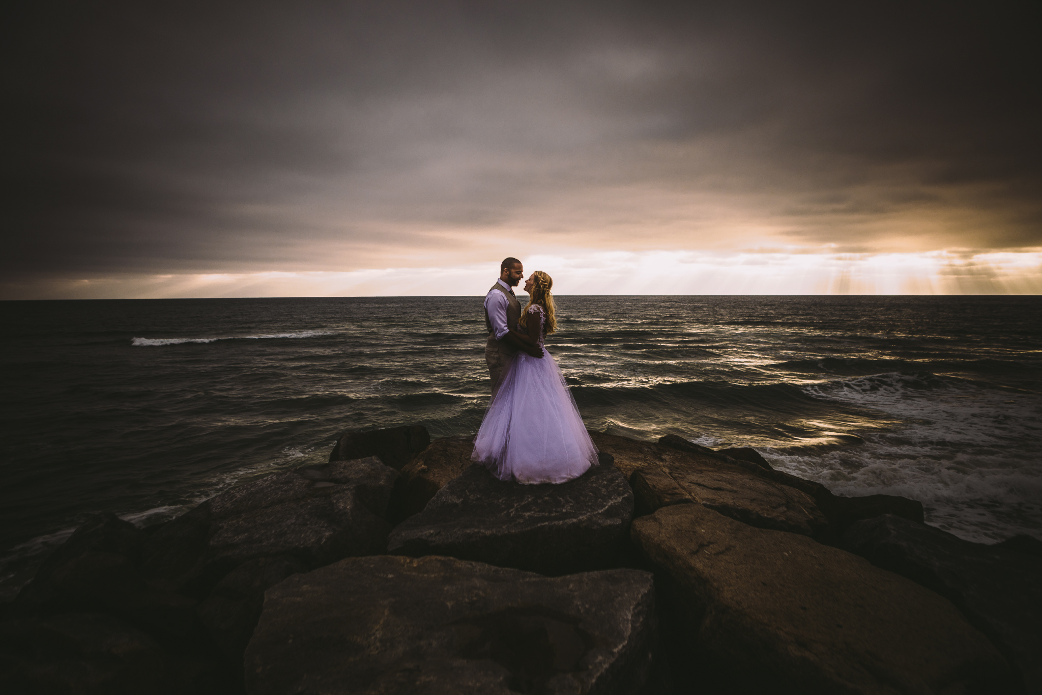 san diego wedding   photographer | groom in beige vest holding bride in white holding each other   with sunrays seen from afar