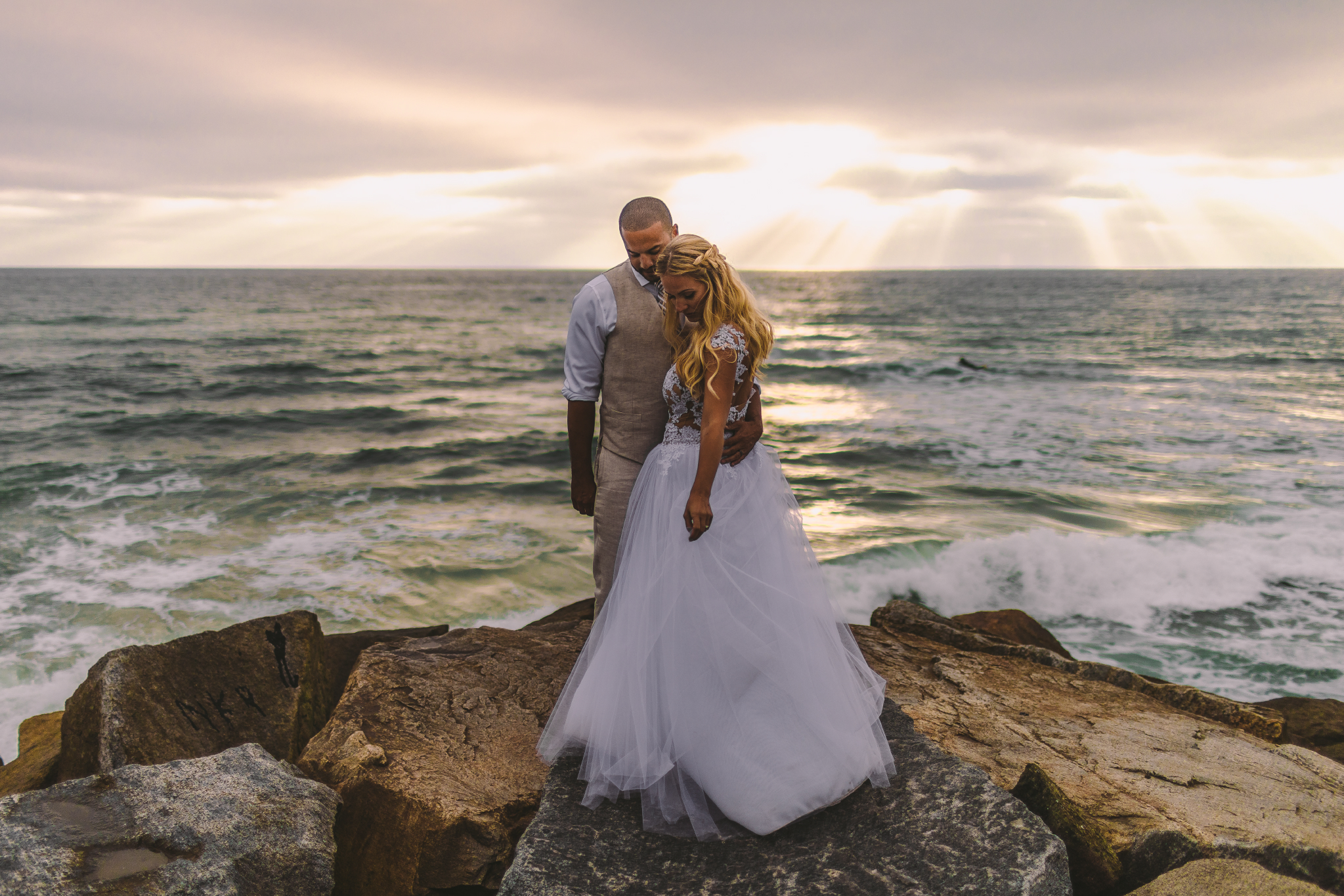 san diego wedding   photographer | married couple standing in front of each other with man's arm   around woman's waist while they both look down with sunrays visible in   background