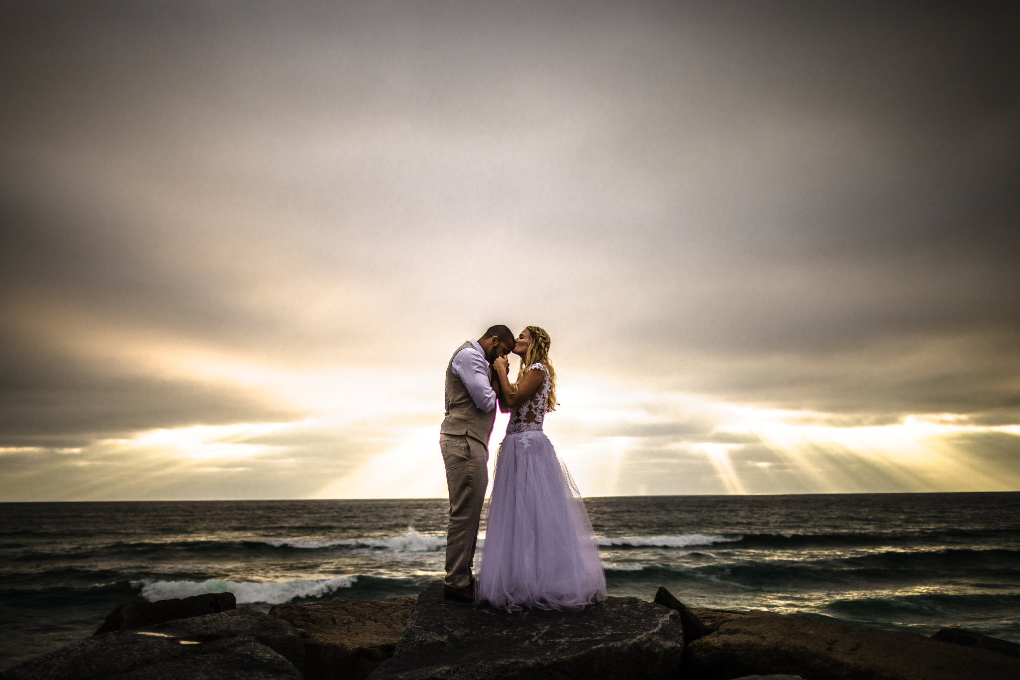 san diego wedding   photographer | married couple with woman kissing man's forehead while holding   his hand with sunrays visible from afar