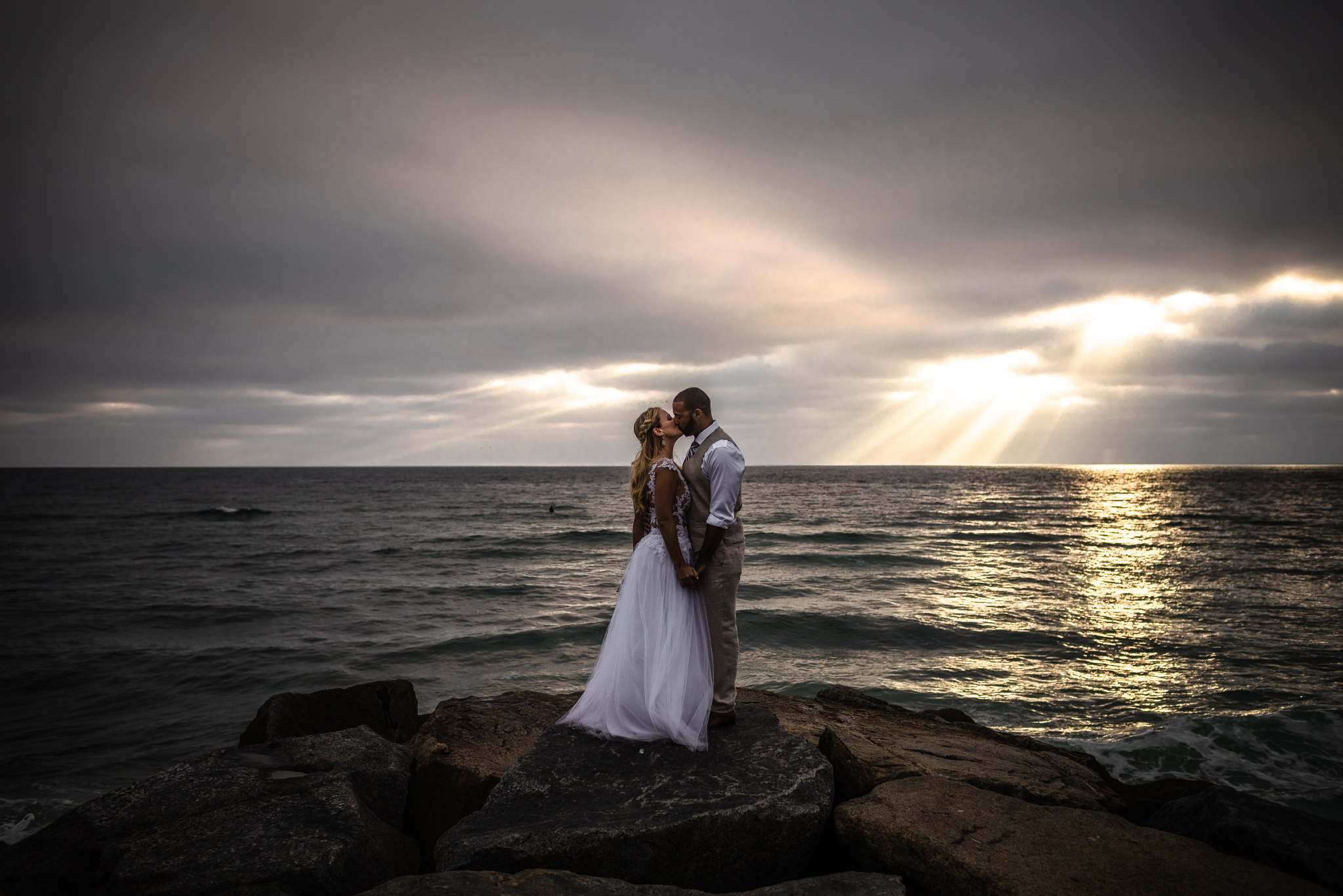 san diego wedding   photographer | married couple with woman on left kissing with sunrays visible   from afar