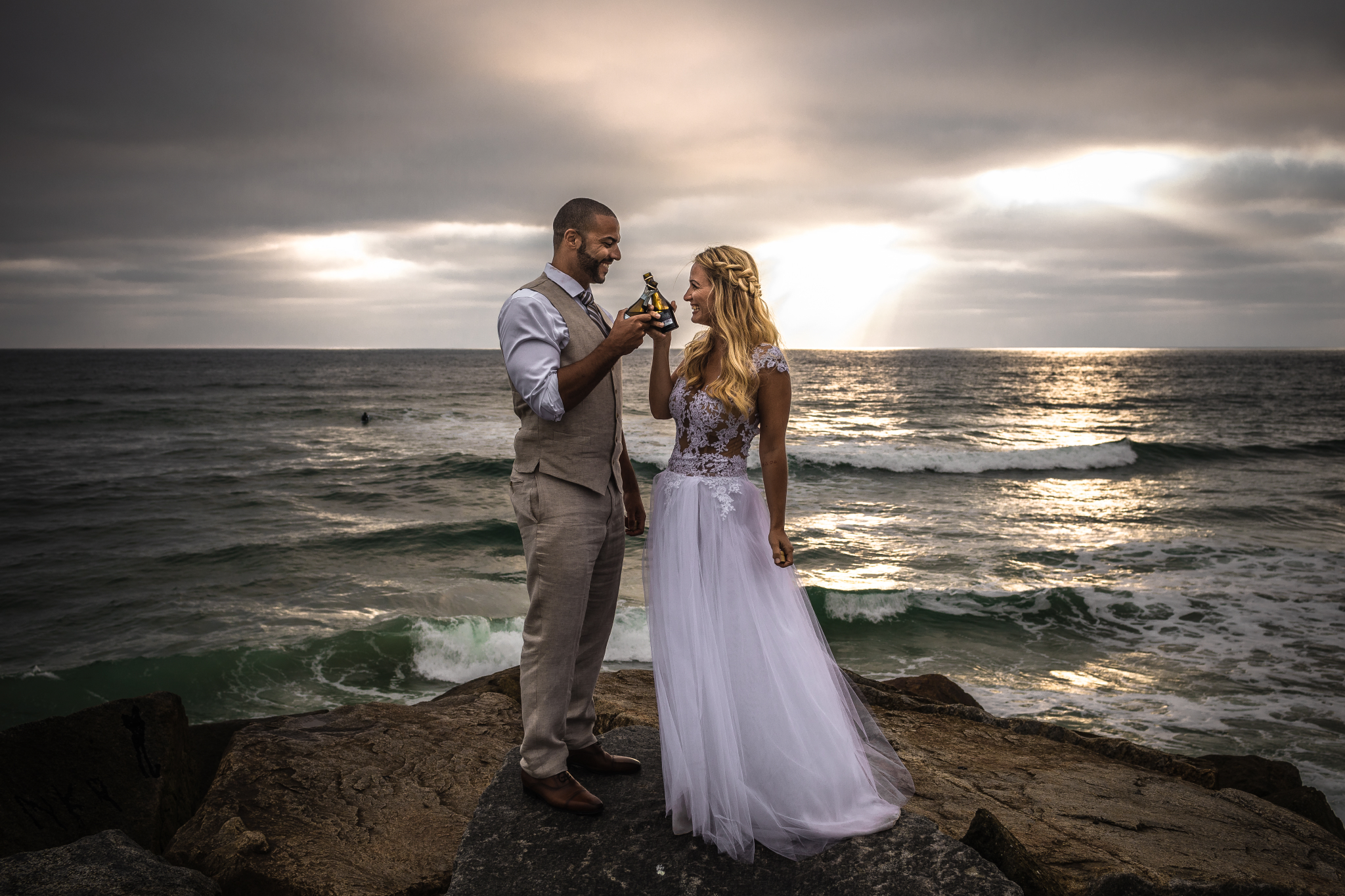 san diego wedding   photographer | married couple holding bottles while smiling at each other
