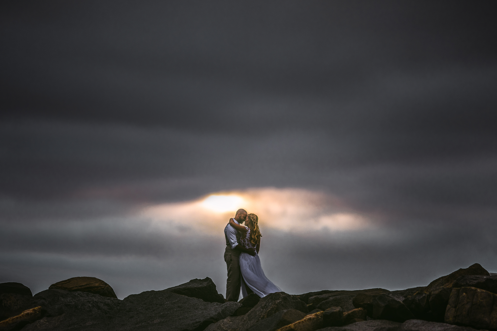 san diego wedding   photographer | married couple with woman's arm around man's neck and man's   arms around woman's waist with dark clouds behind them