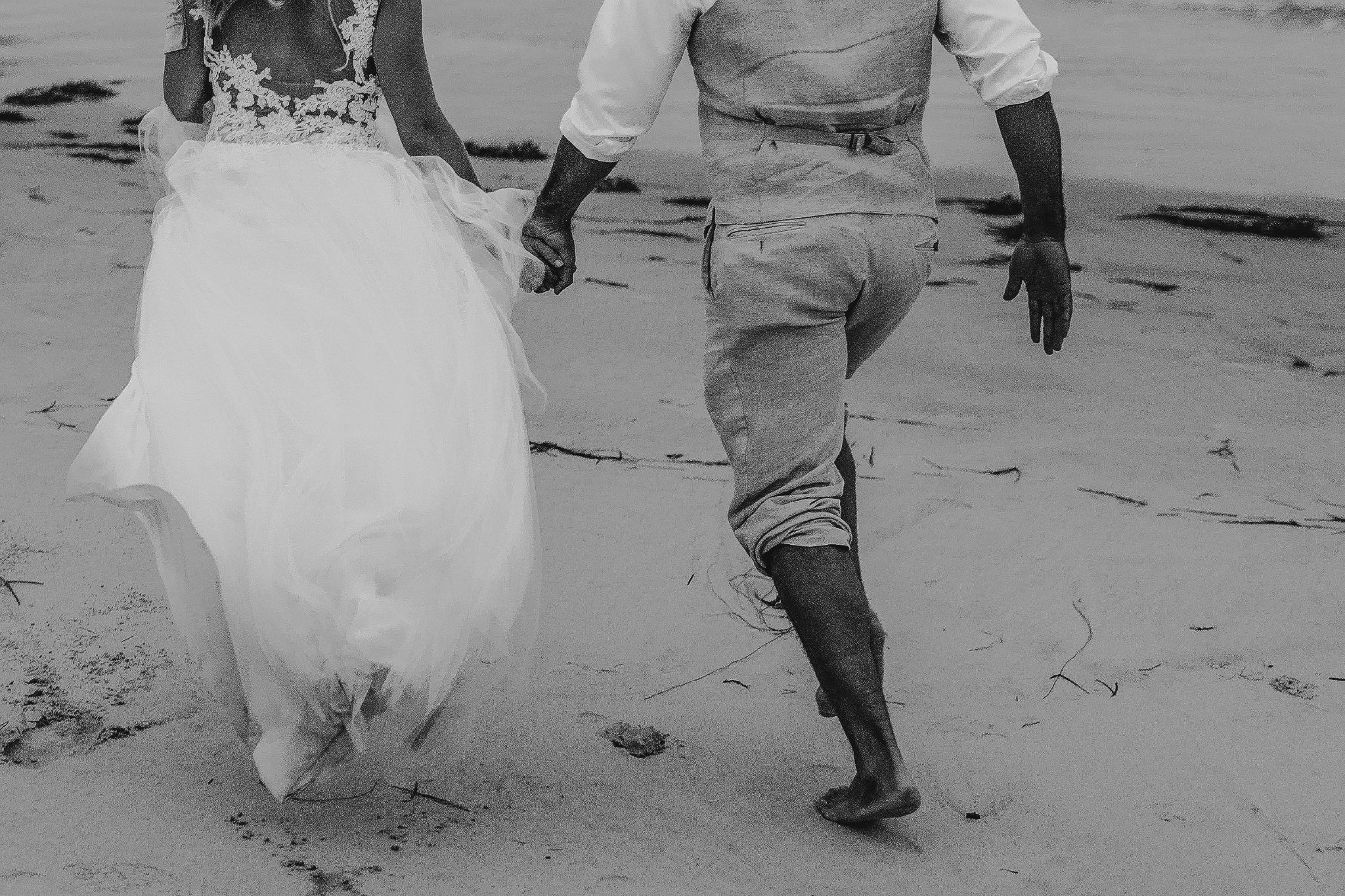 san diego wedding   photographer | black and white shot of couple holding hands and walking away   on sandy beach
