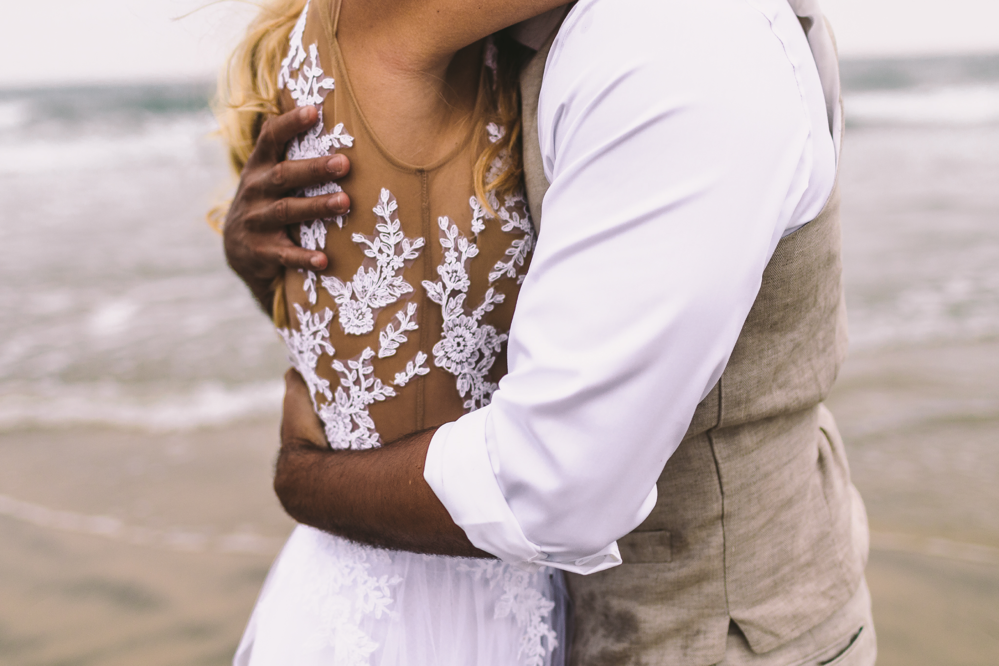 san diego wedding   photographer | shot of married couple's torso while they hug on beach shore