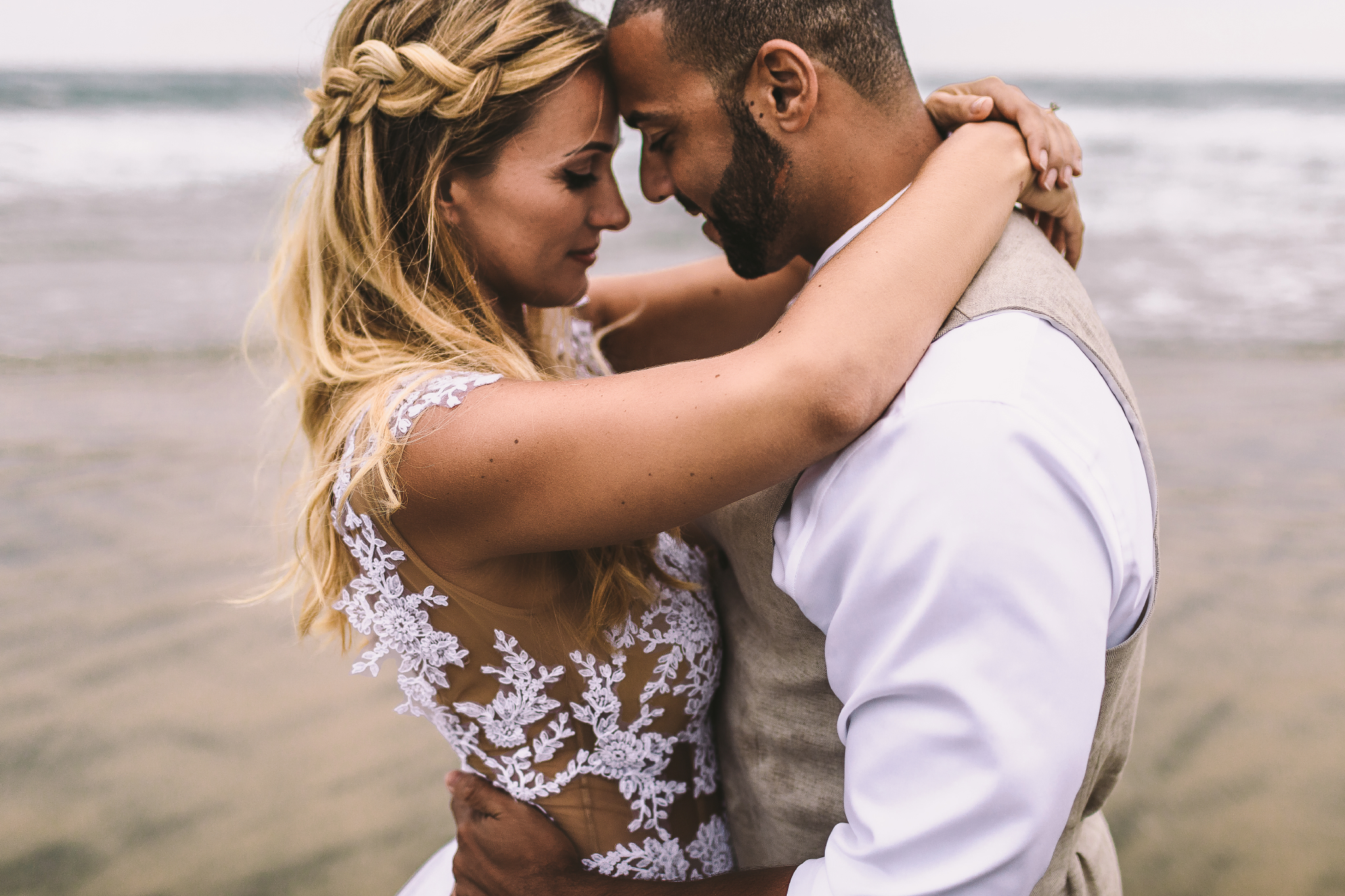 san diego wedding   photographer | married couple holding each other with beach shore in   background