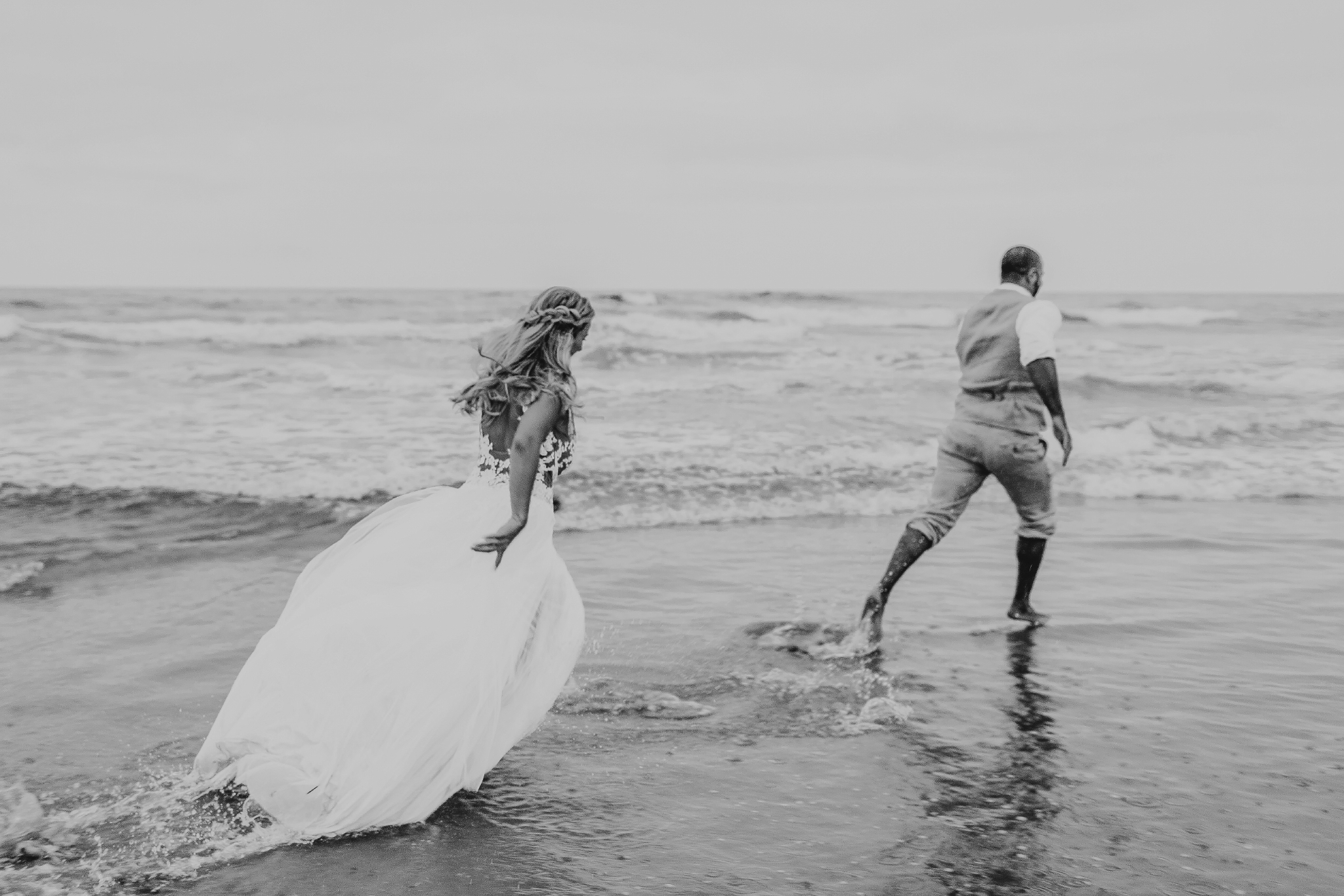 san diego wedding   photographer | black and white shot of married couple chasing each other on   seawater
