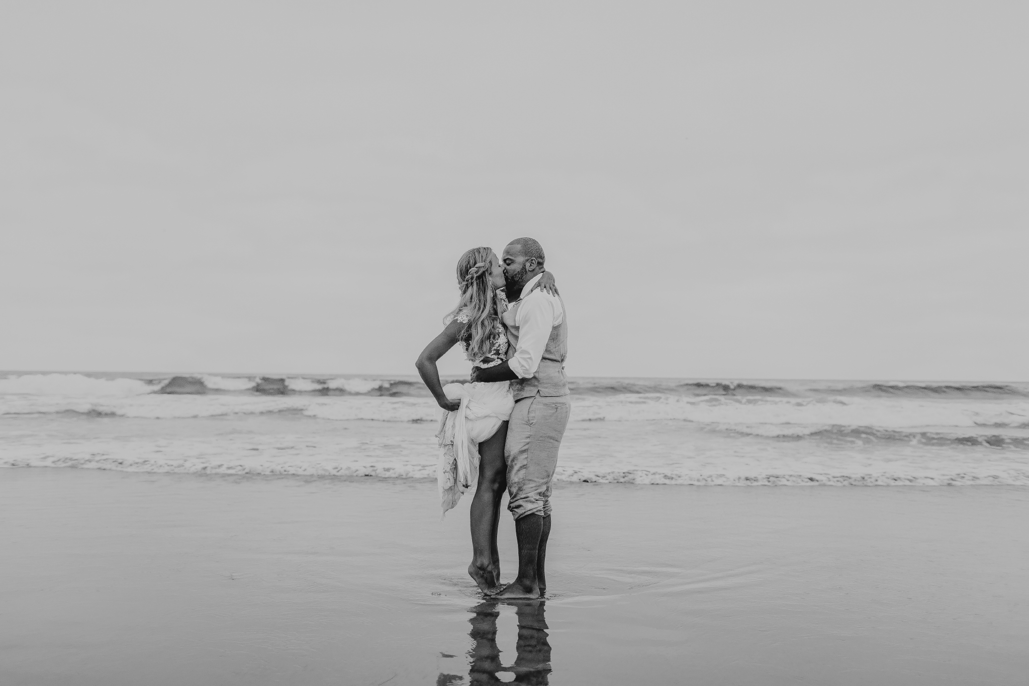 san diego wedding   photographer | married couple kissing on beach shore with bride holding her   dress up