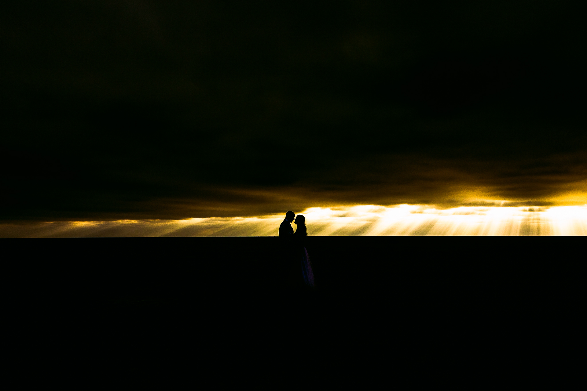 san diego wedding   photographer | silhouette of couple about to kiss with a lot of sunrays   visible in the background