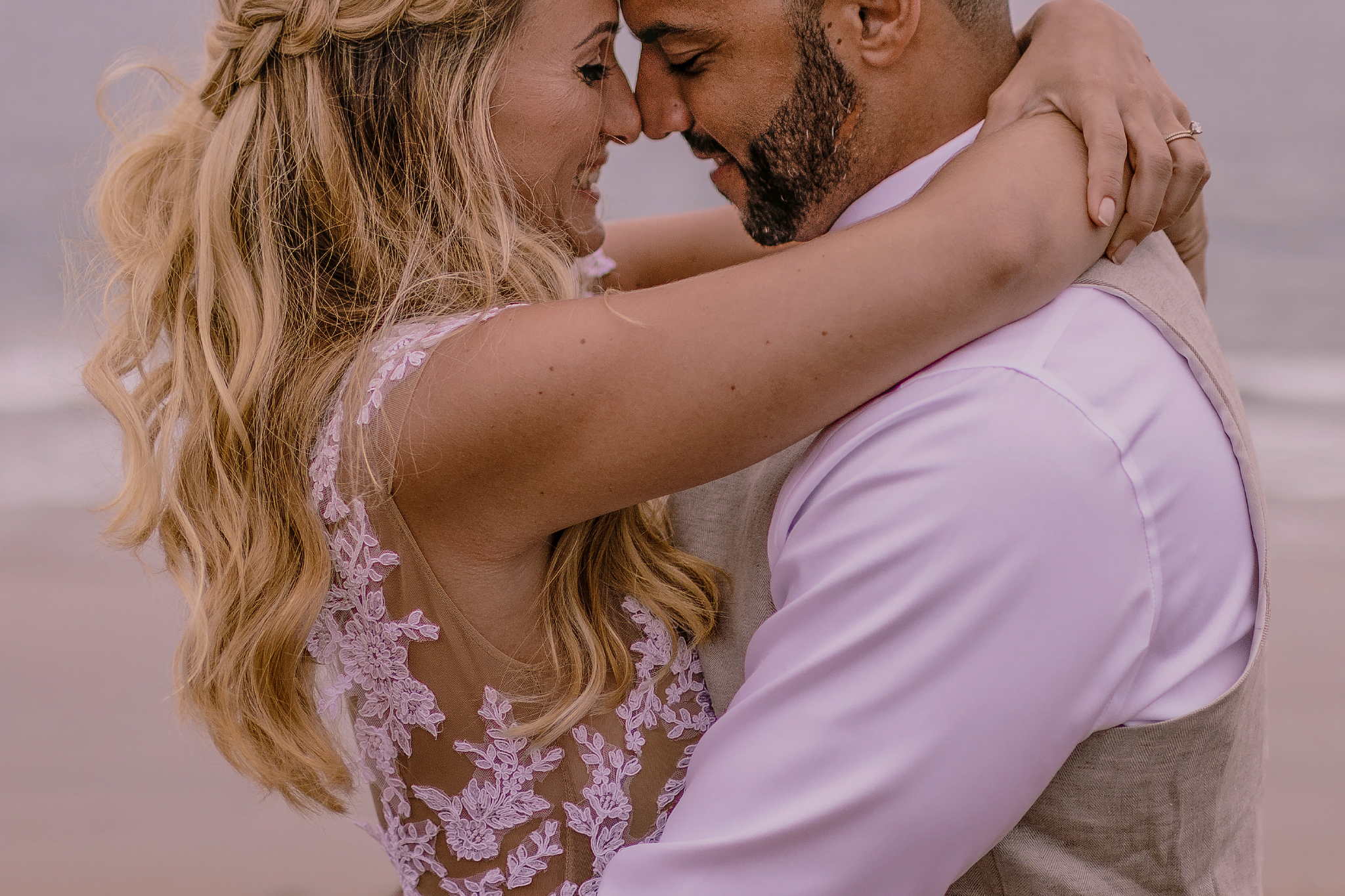 san diego wedding   photographer | couple holding each other with woman's arms around man's neck   and man's arms around woman's waist by the sea
