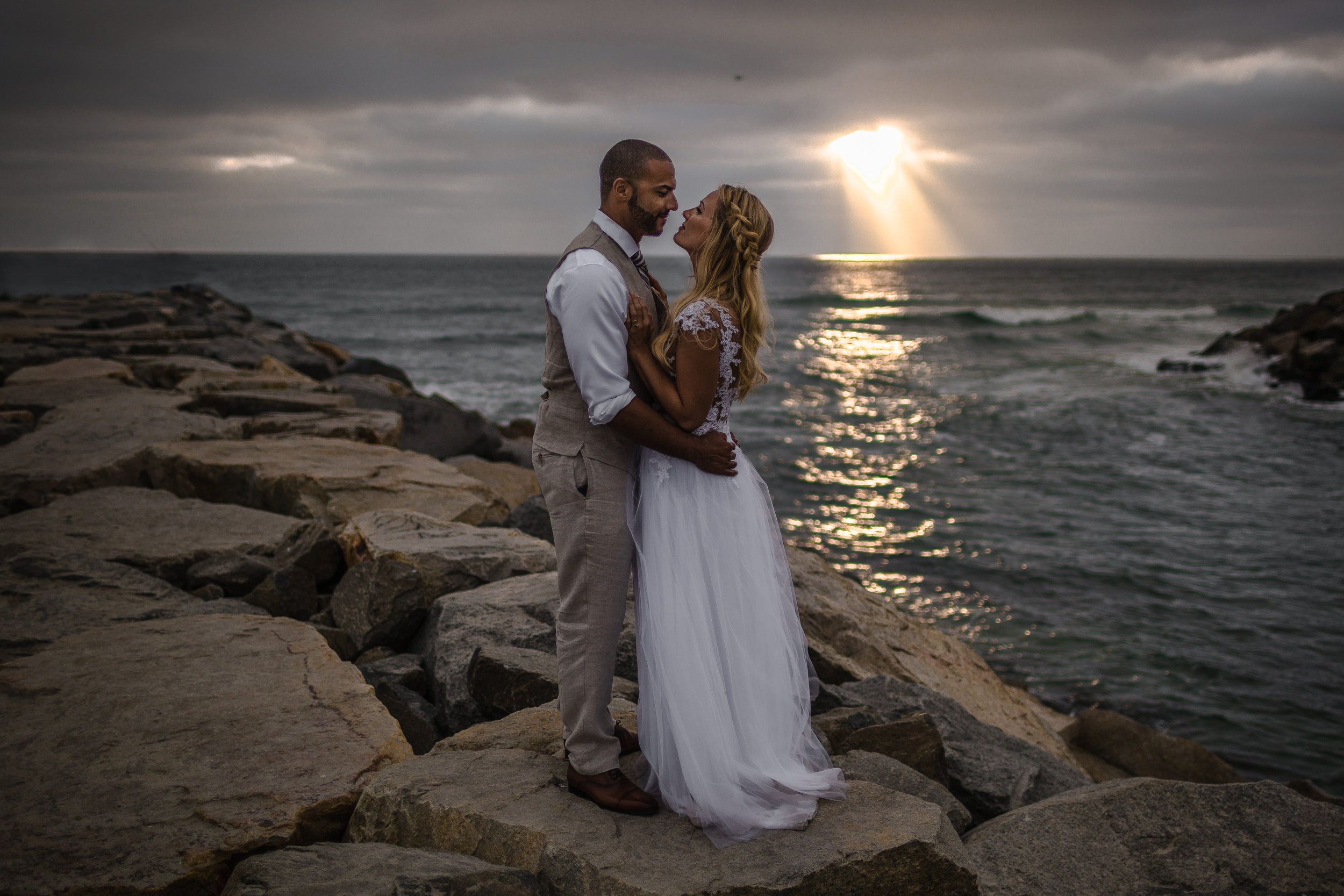 san diego wedding   photographer | groom holding woman by the waist with woman's hands on man's   chest on rocky shore with sunrays visible from afar