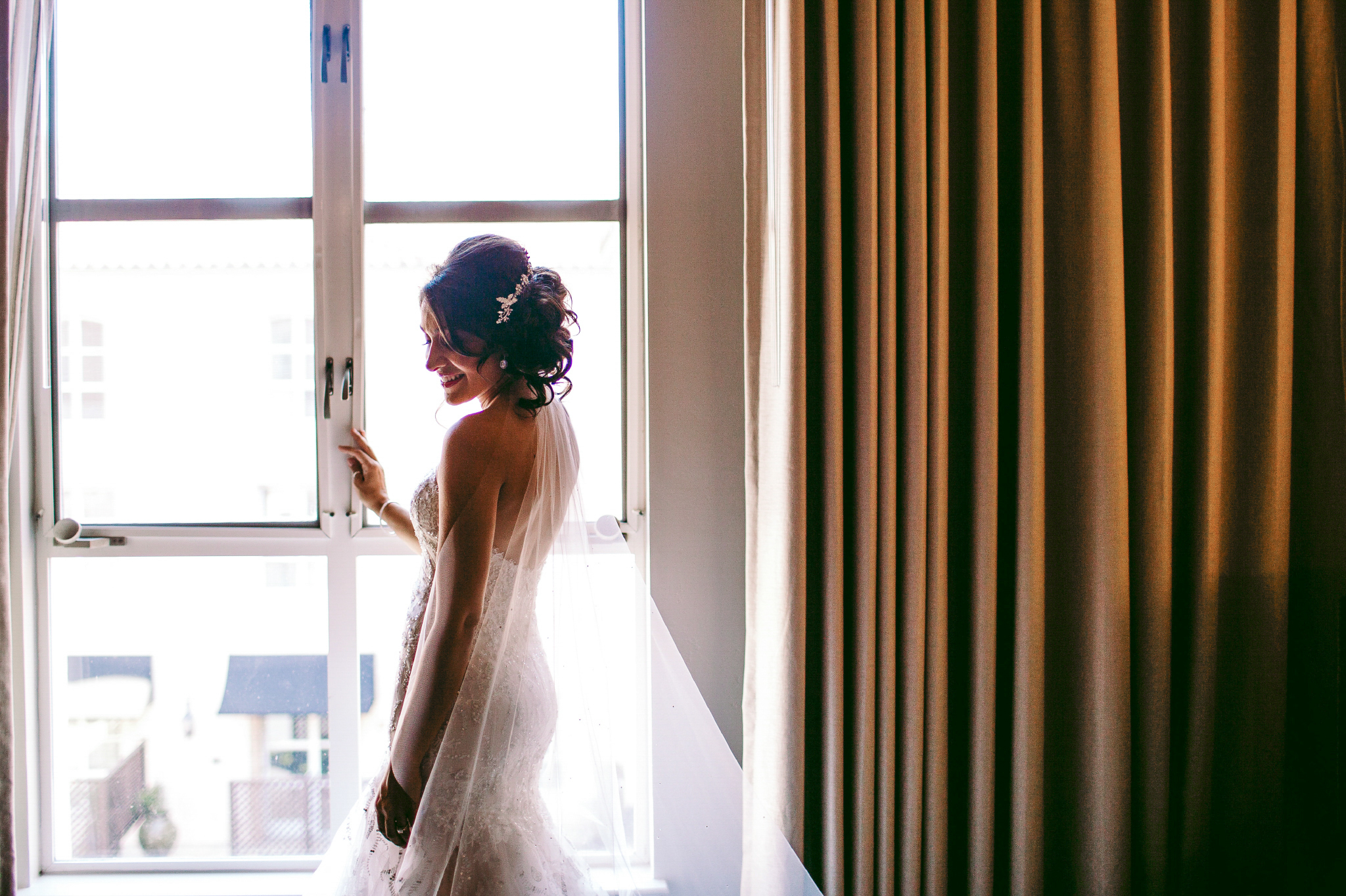 san diego wedding   photographer | woman in wedding dress by the window looking down to her side